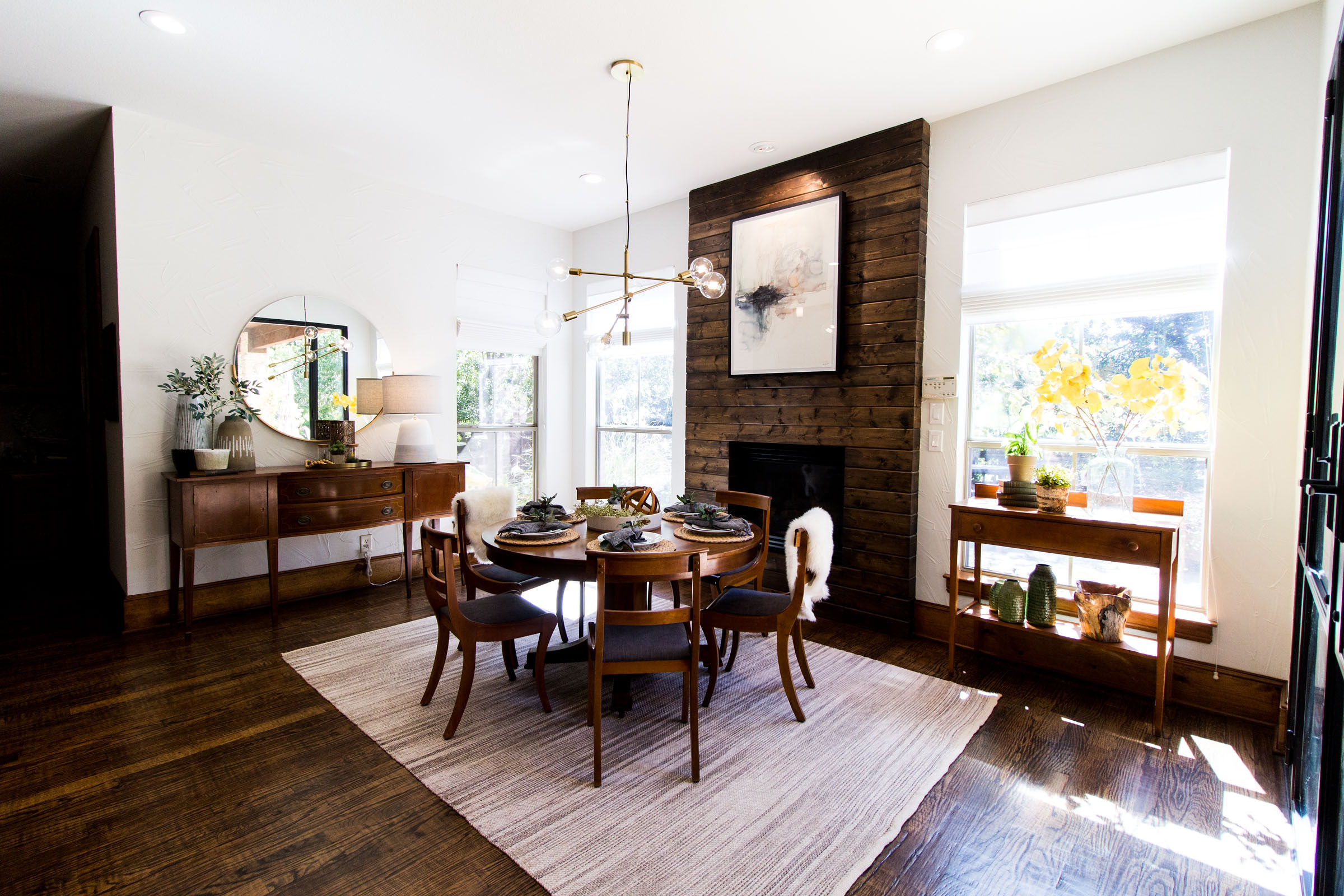 Cozy breakfast nook area with wood fireplace, iron framed patio doors, grey area rug, staged table, exposed bulb lighting, minimalistic decor