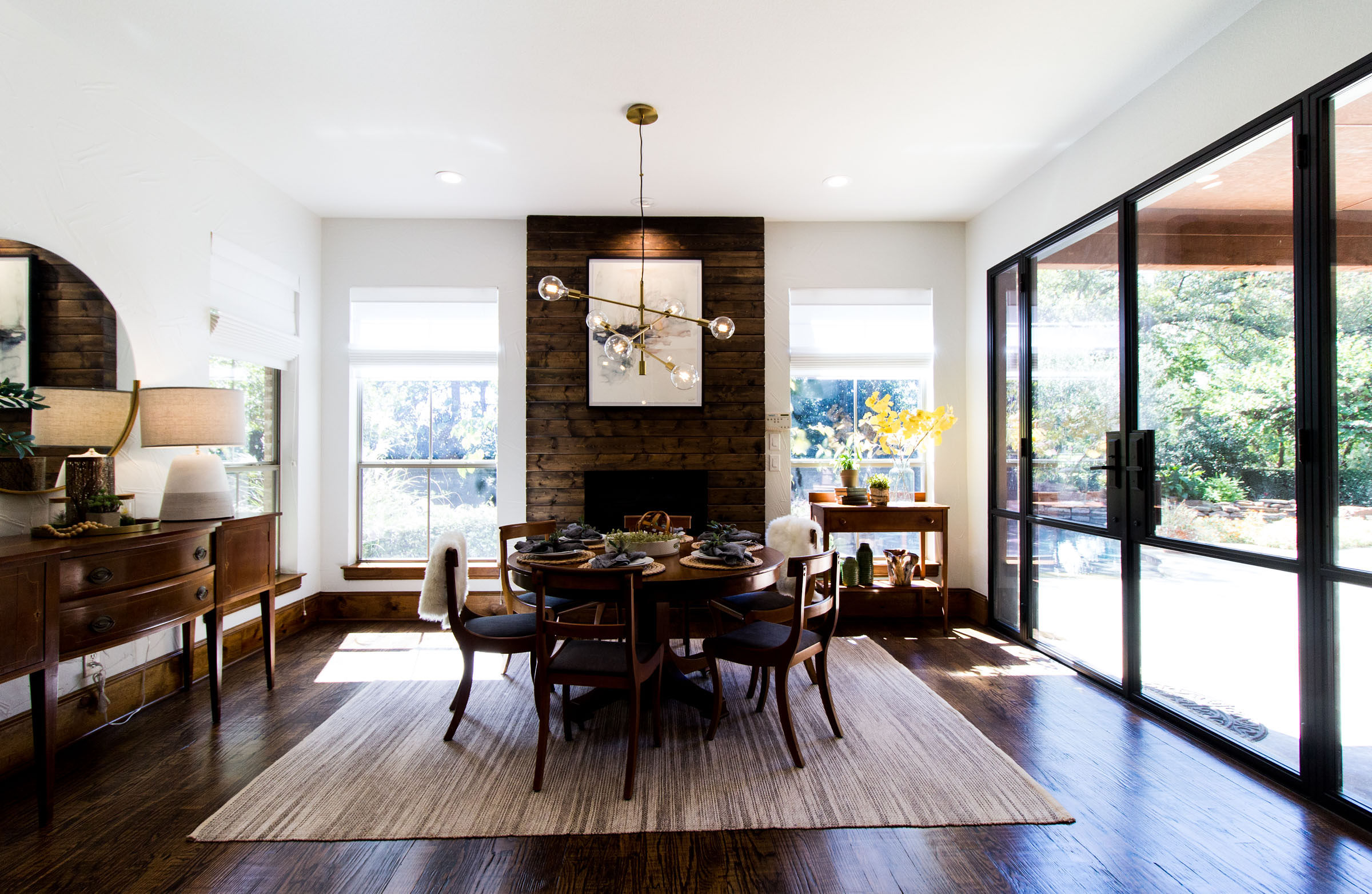 Cozy breakfast nook area with wood fireplace, iron framed patio doors, grey area rug, staged table, exposed bulb lighting