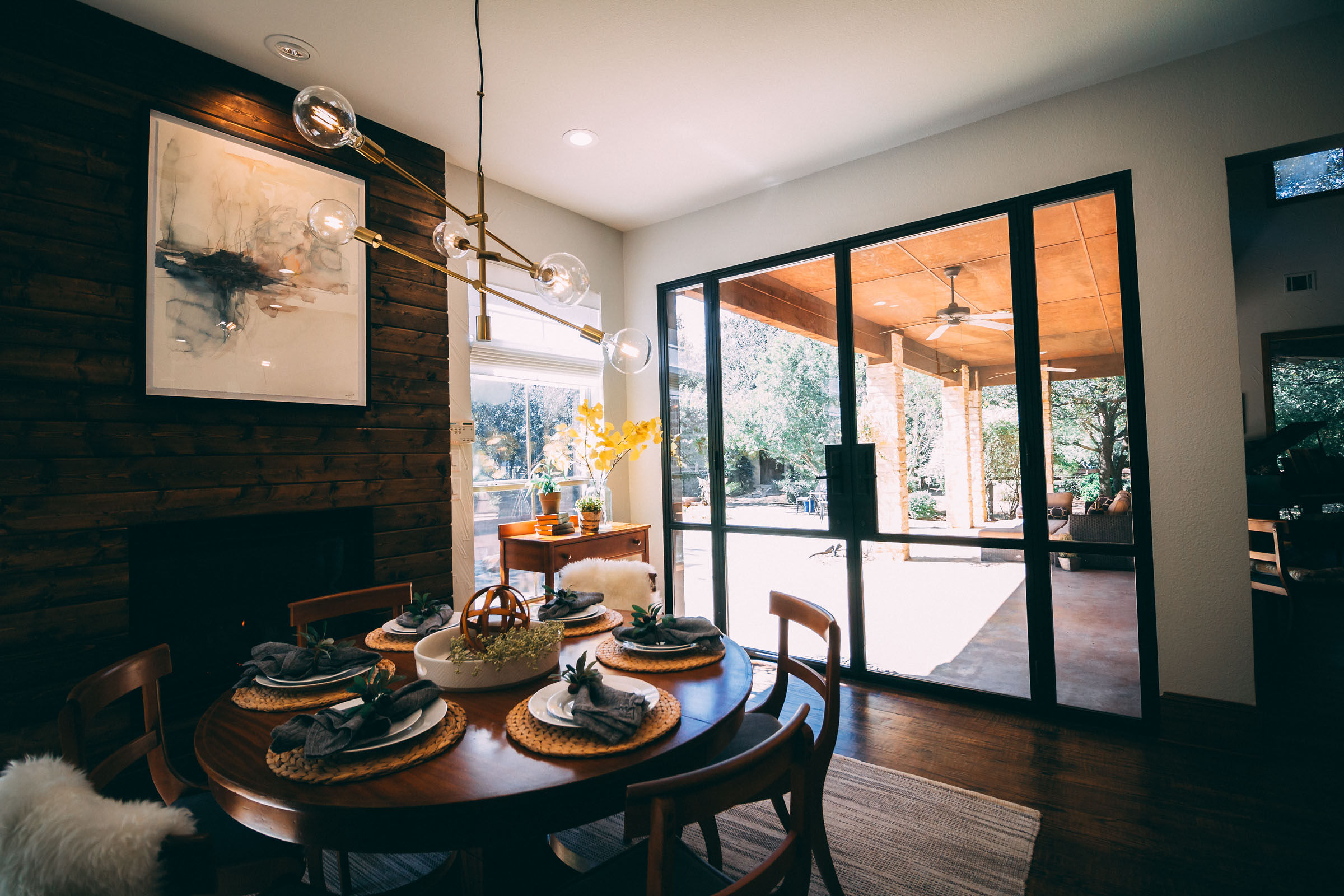 Picture of a breakfast nook, table set, big doors onto patio, wood fireplace, exposed light bulb chandelier.