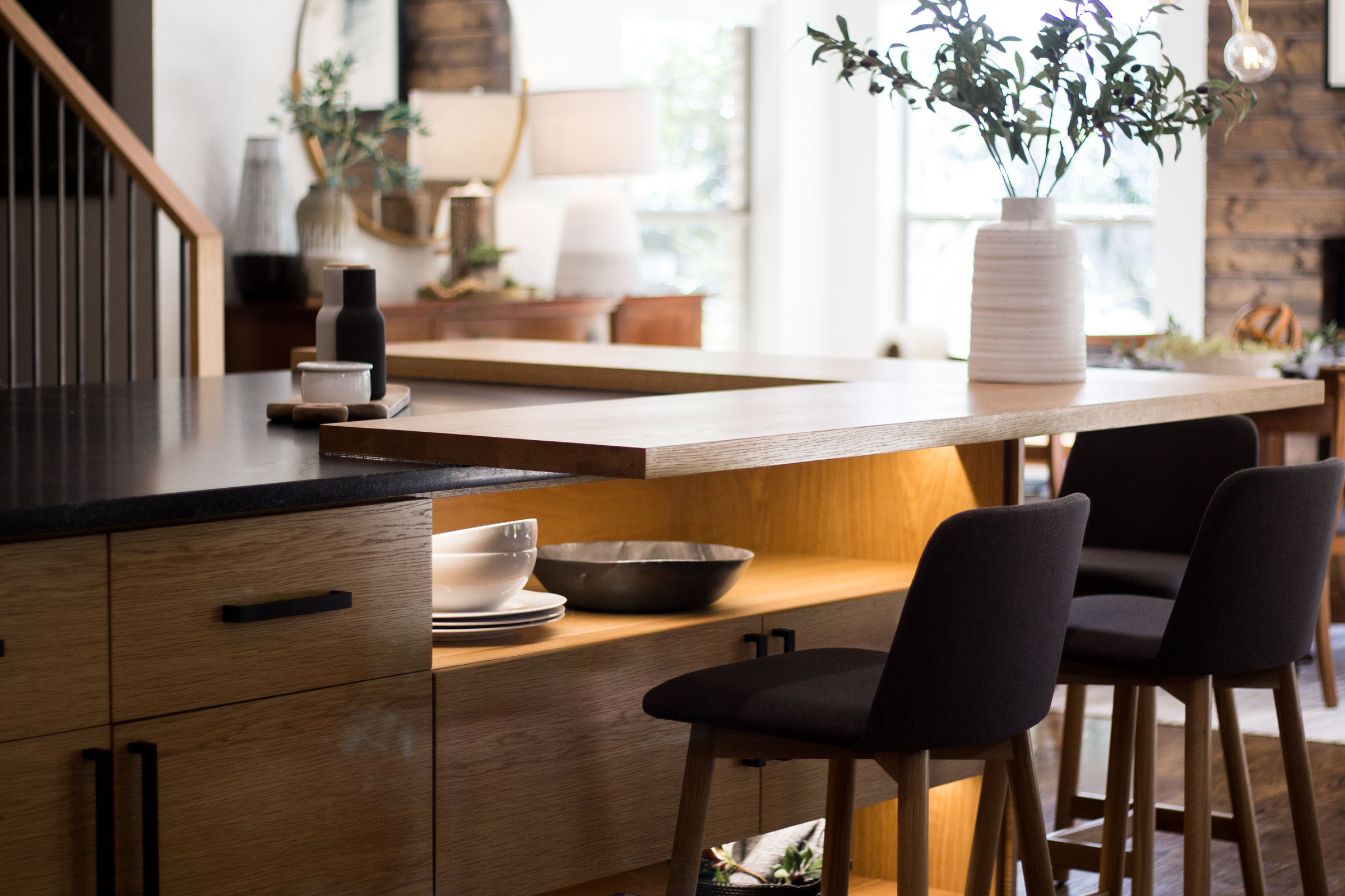 Cabinet under lighting with open cabinet space for kitchen dishes. Blonde wood cabinets, black cloth bar stools, plants, open floor plan.