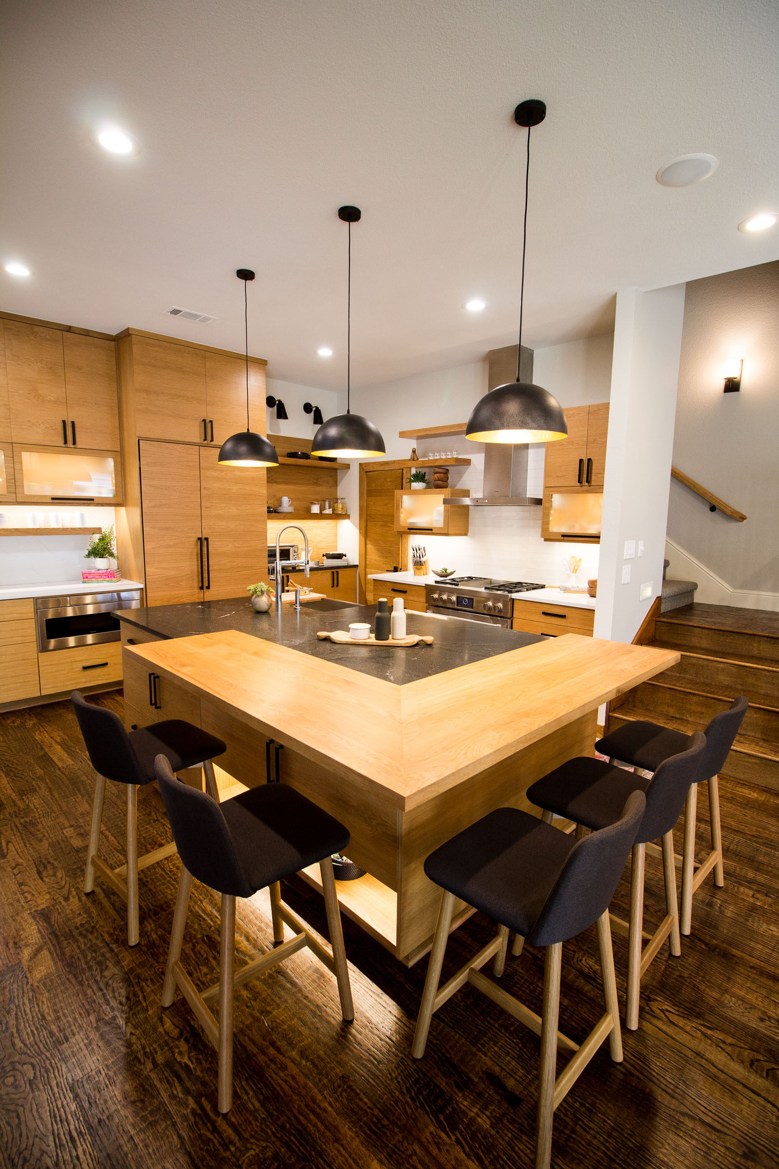 Warm tones, industrial vibe, simple, open floor plan, raw wood, blonde cabinets, hard wood floors, under lighting