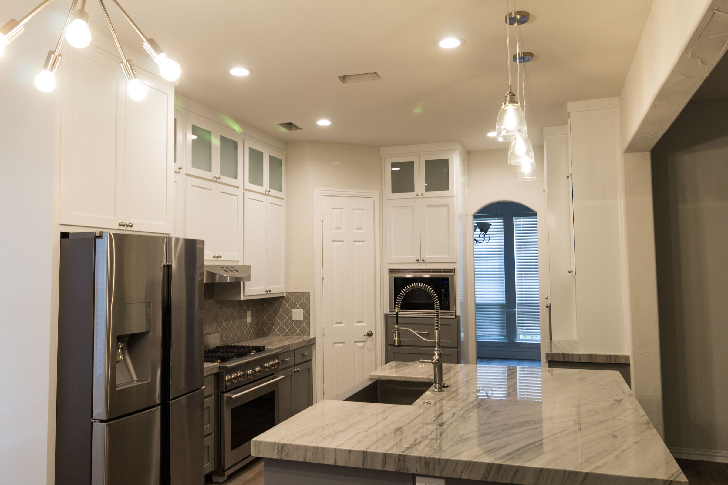 Contemporary kitchen remodel with exposed bulb lighting in the breakfast nook, kitchen island, stainless steel appliances