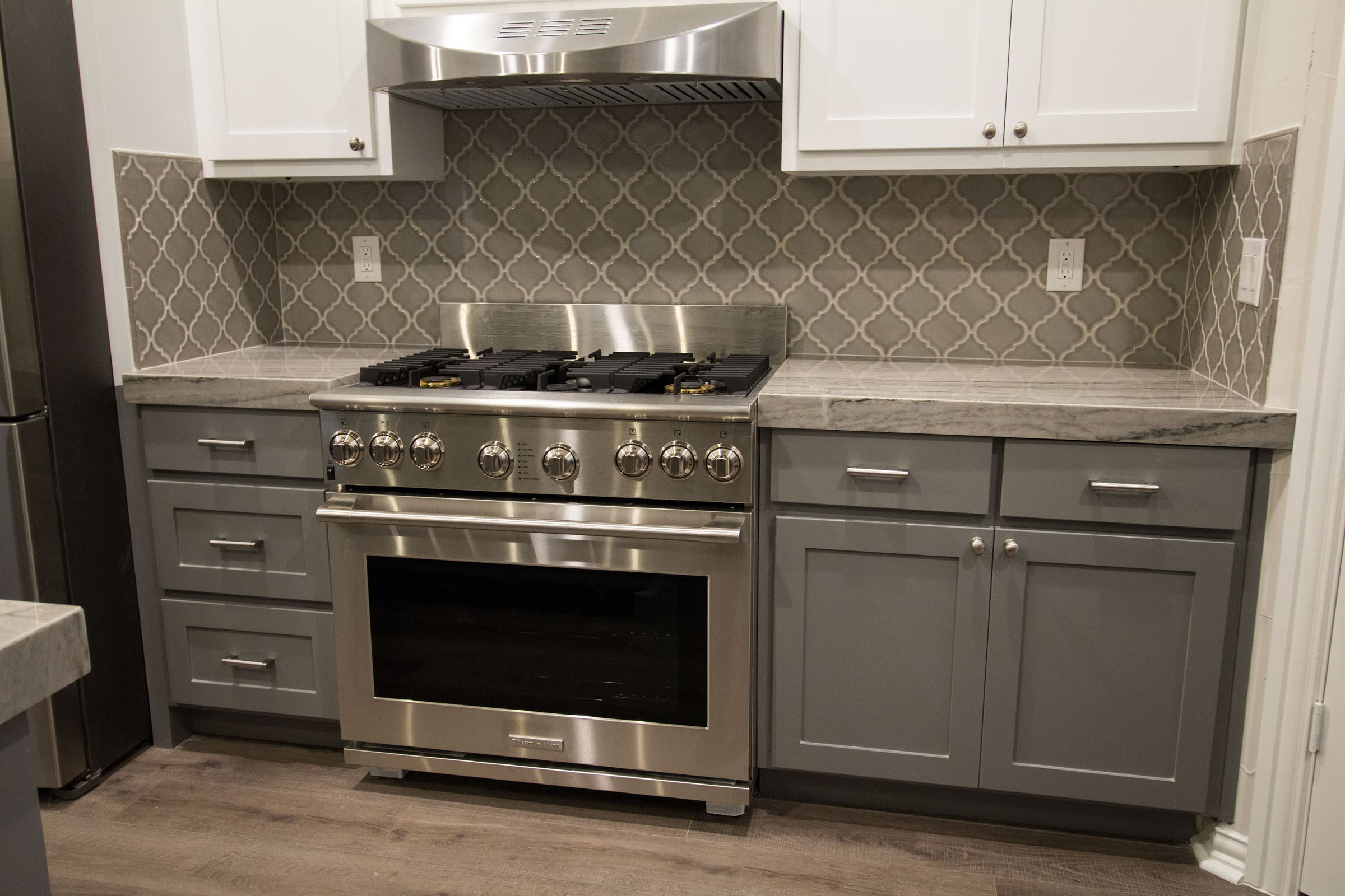 Contemporary kitchen remodel with industrial stainless steel gas cooking range, arabesque tile, grey shaker cabinets, white uppers, grey granite