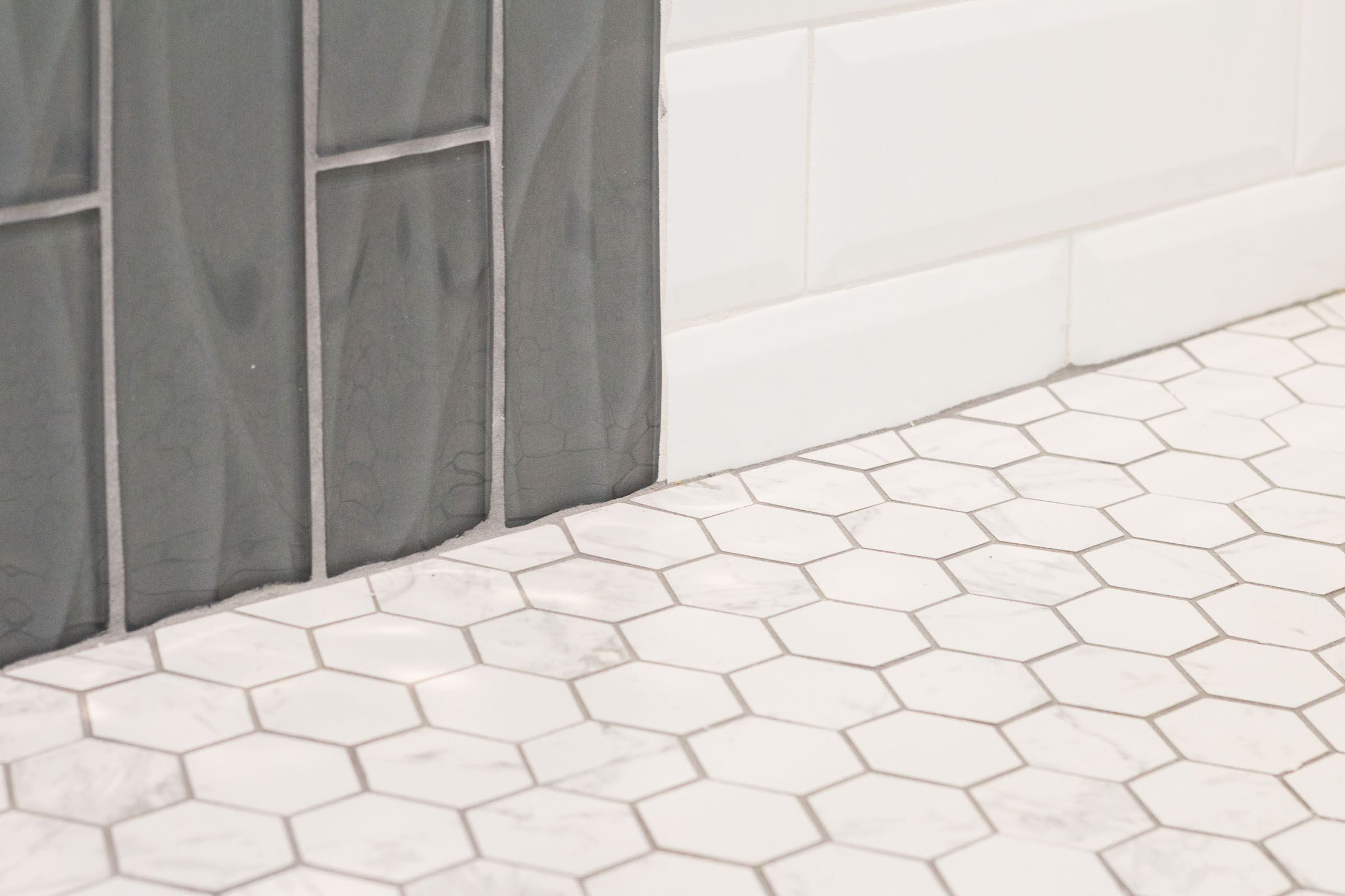 Close up picture of shower tile with grey vertical glass subway tile, white horizontal subway tile, and octogonal floor tile