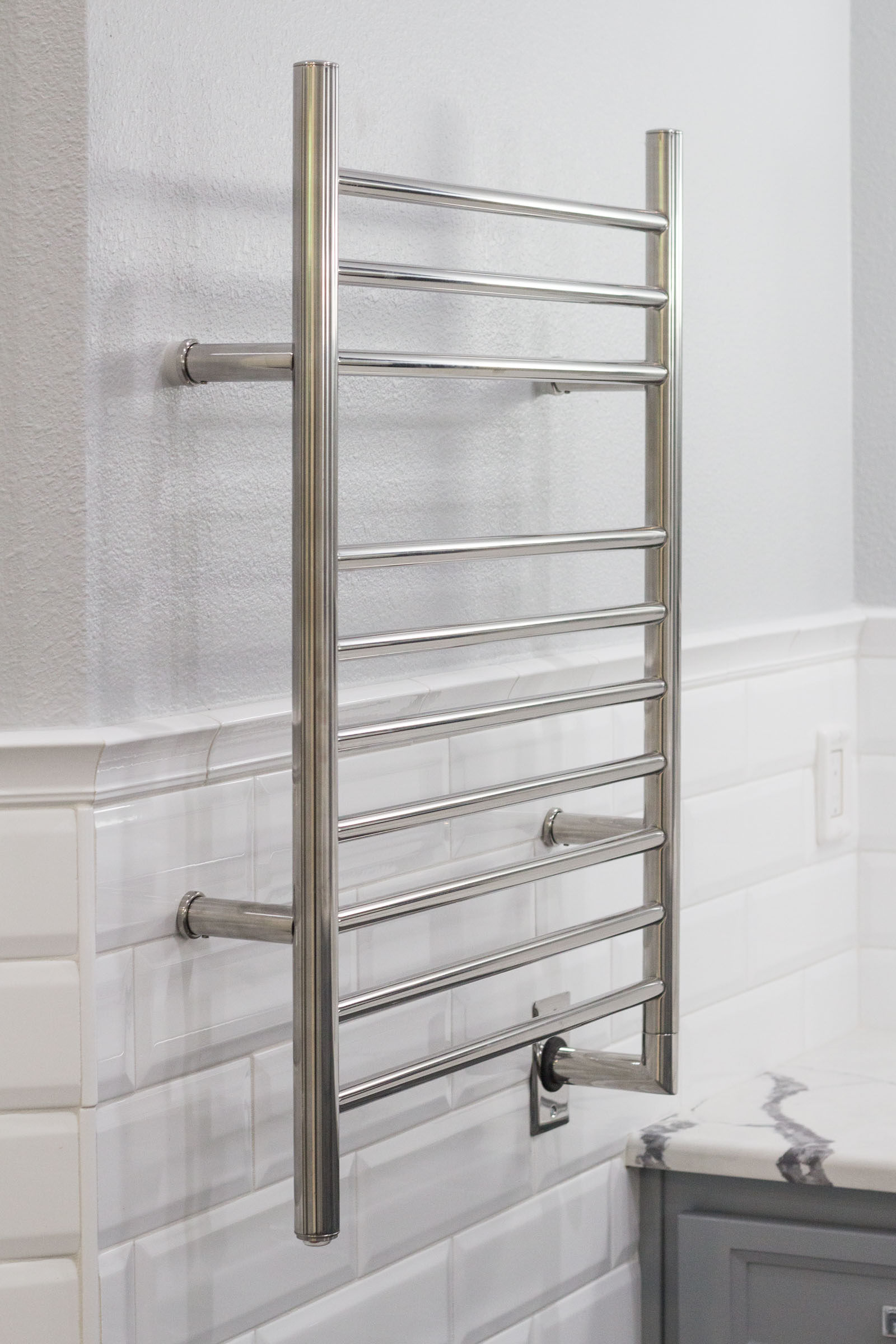 Chrome towel rack with white subway tile backsplash and light grey walls