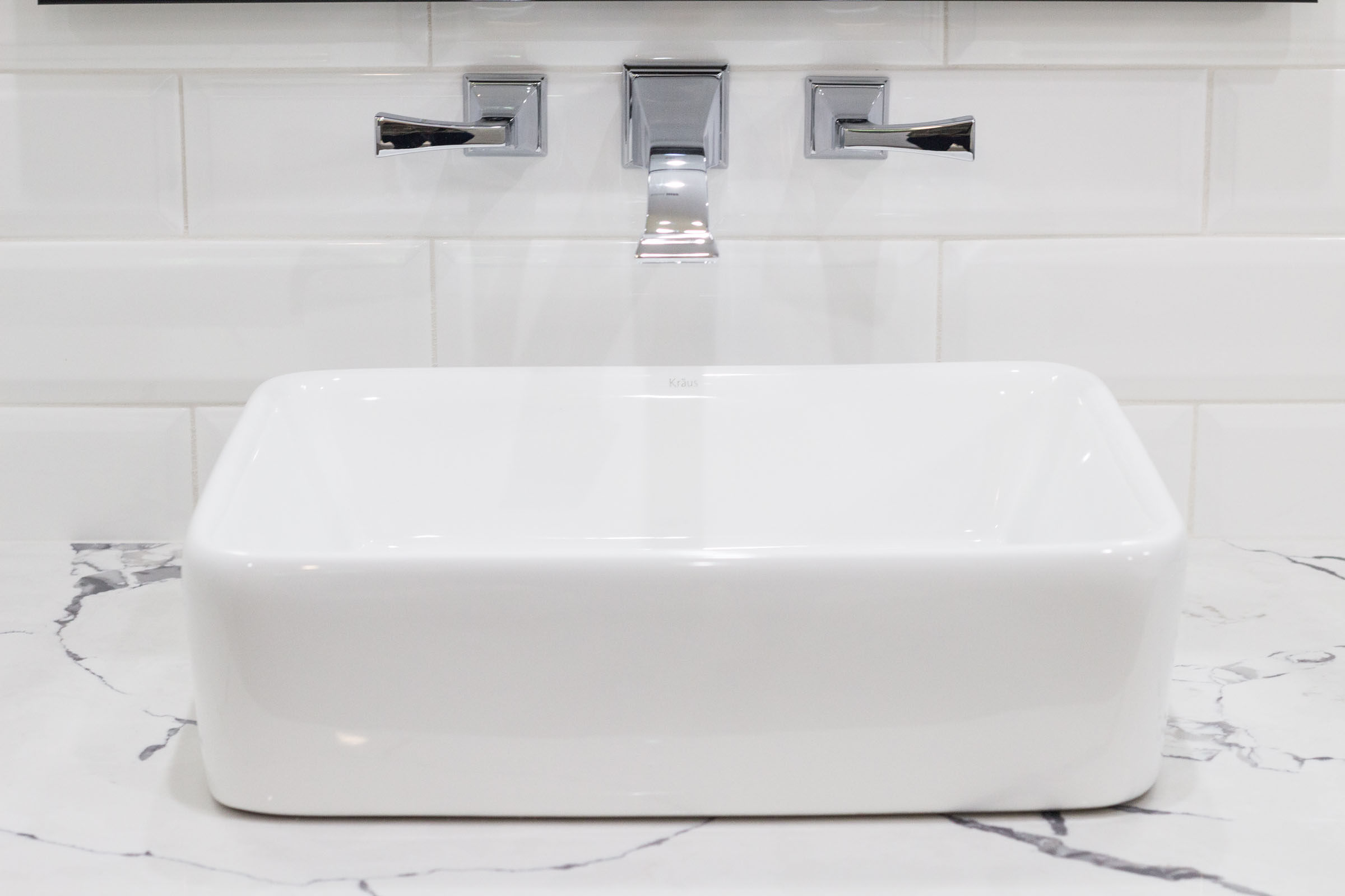 Countertop pedestal bathroom sink with white and grey granite, chrome sink faucet, and white subway tile backsplash