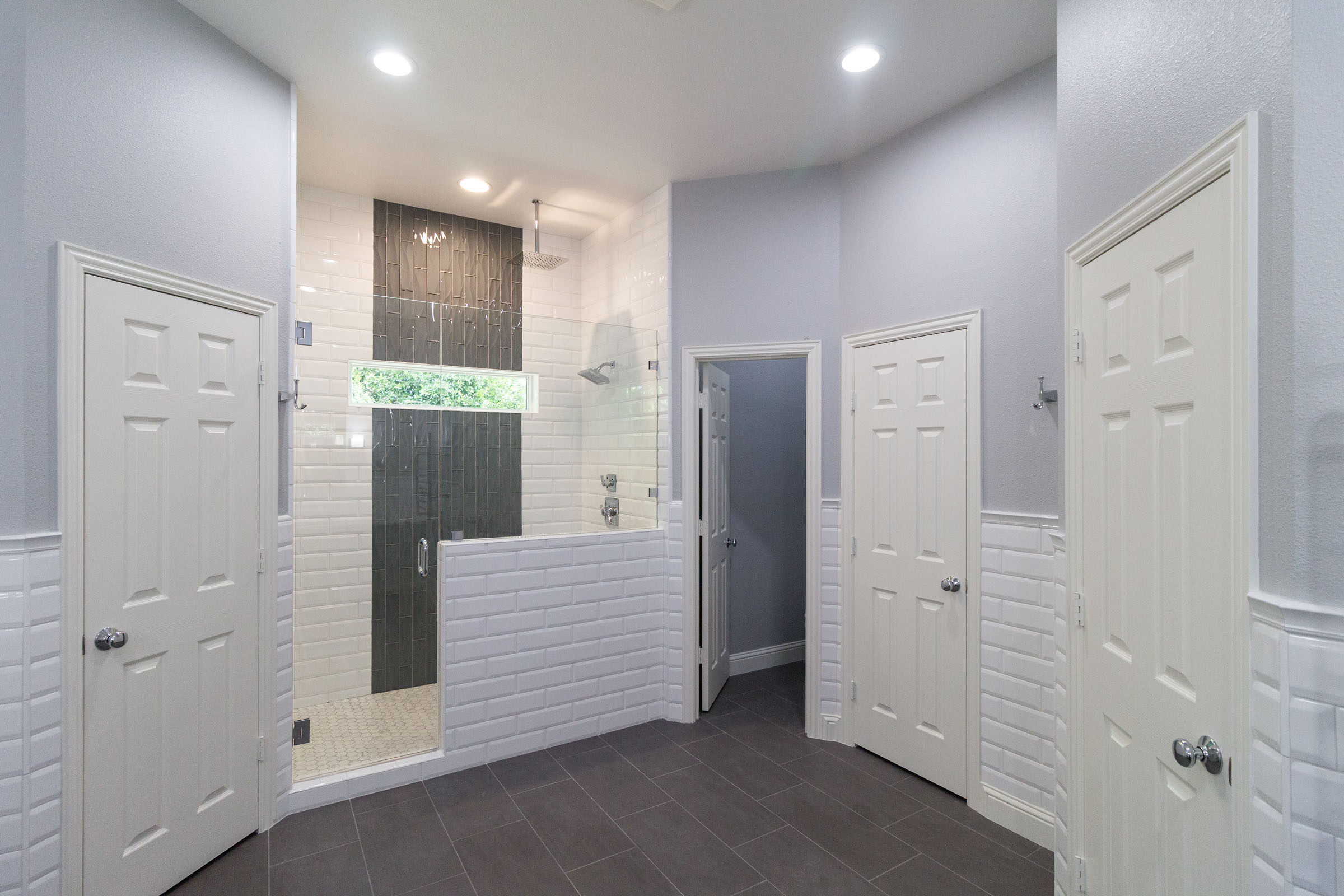 Bathroom remodel with white subway tile, dark grey flooring, walk in shower, open concept