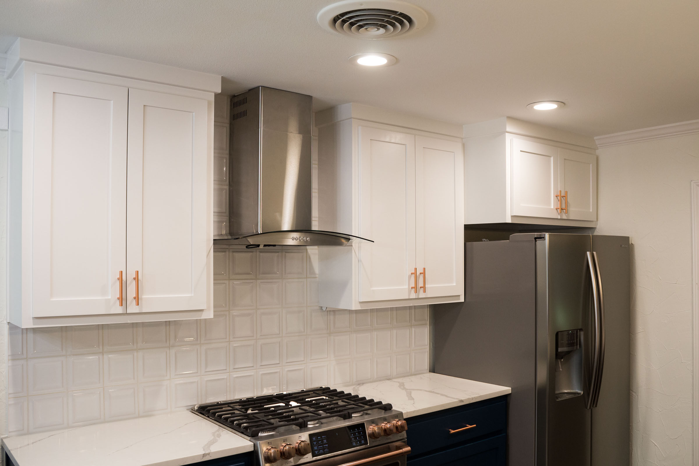 Stainless steel vent hood, copper hardware, white upper cabinets, navy lower cabinets
