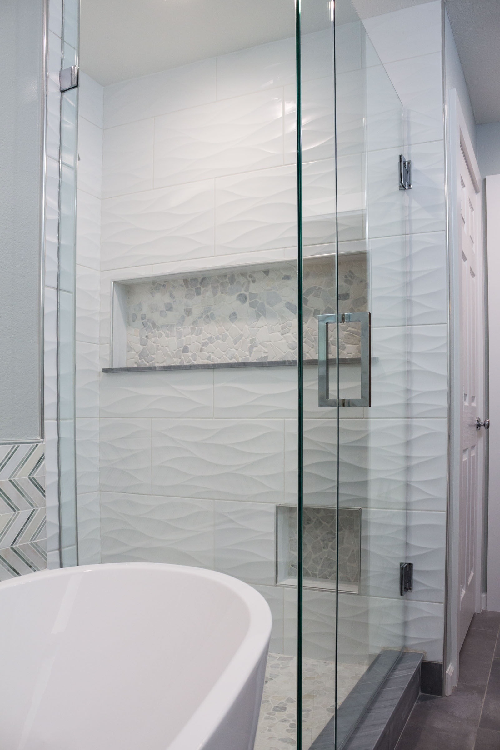 Bathroom remodel with walk in shower, glass doors, pedestal bathtub, and dark grey flooring