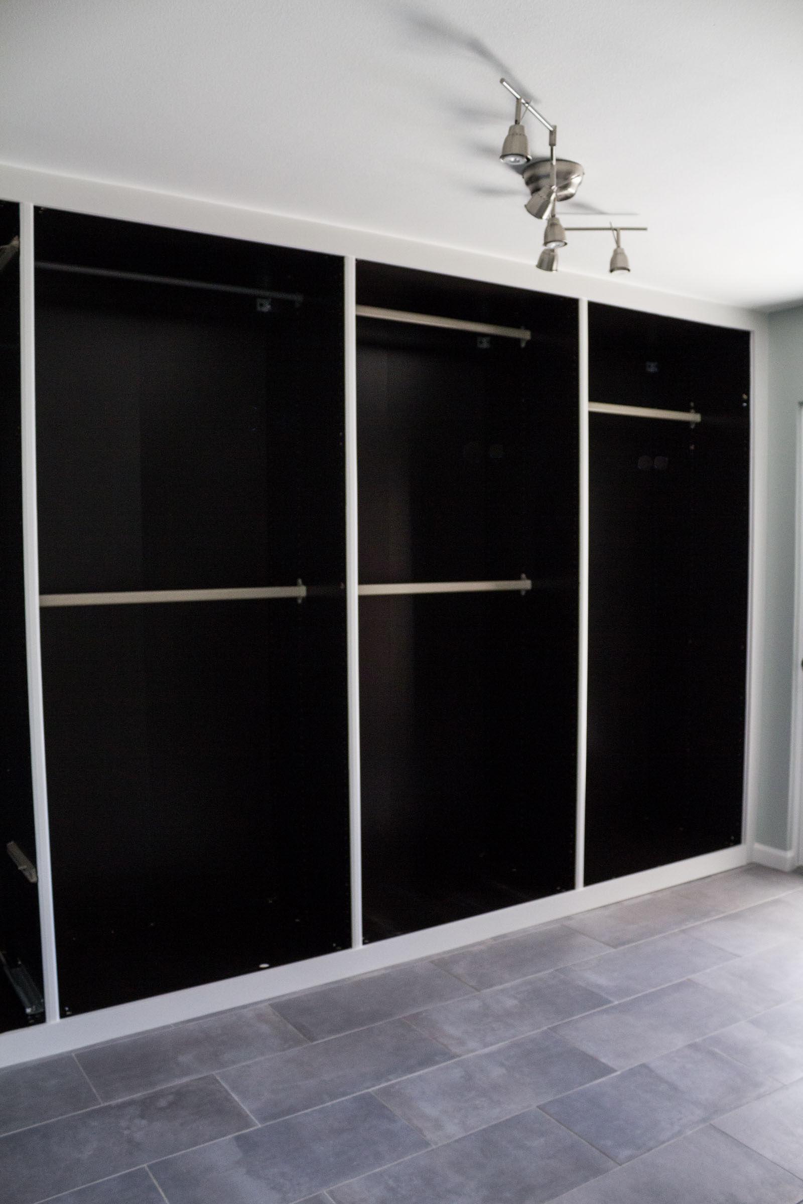 Doorless black bedroom closet built ins with clothing rods