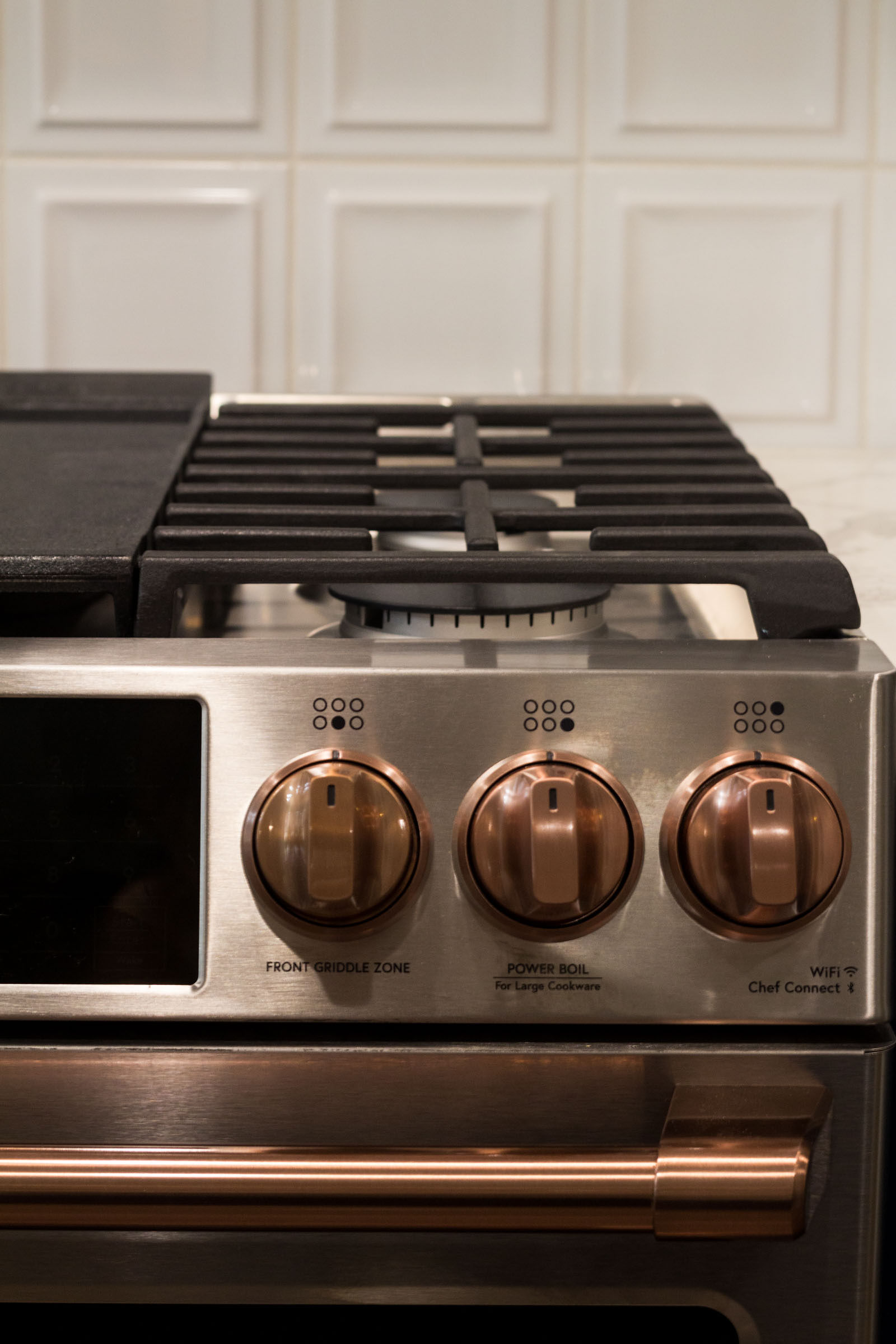 Close up of stainless steel gas cooking range with copper accents and white back splash