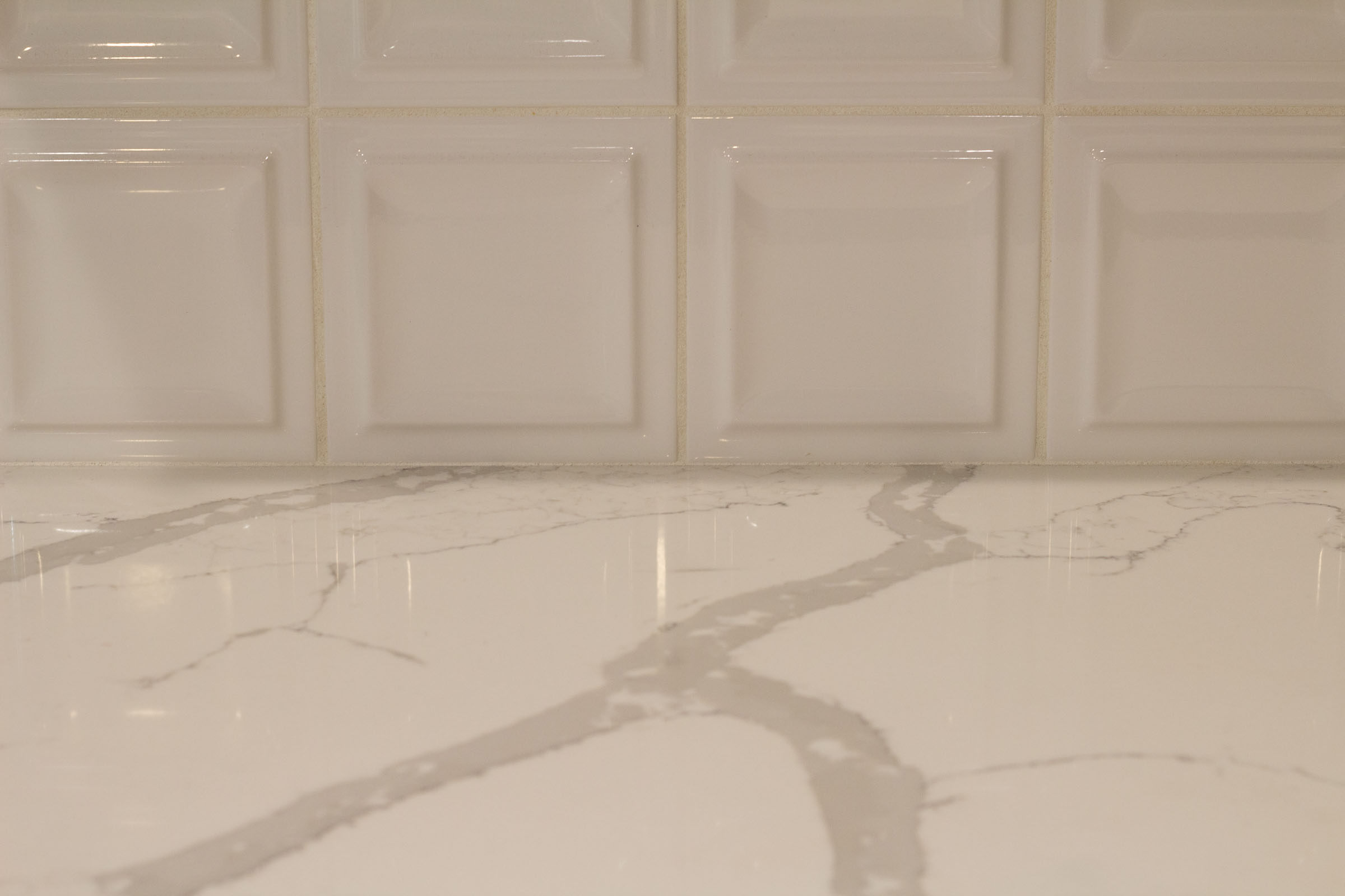 Close up photo of white countertops and square backsplash tiles