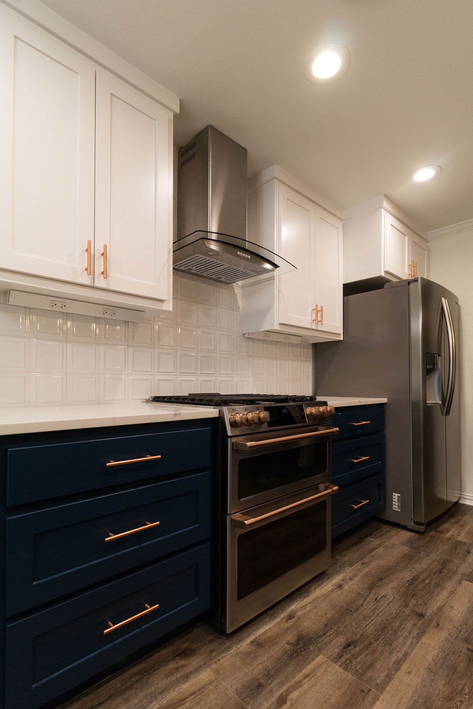 Navy cabinets, copper hardware, white uppers, square backsplash, vent hood, and hardwood floors