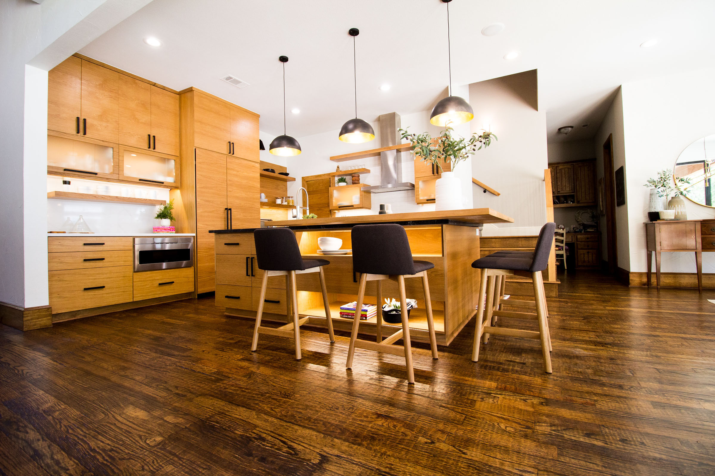 The centerpiece of the kitchen is the unique island with lots of storage, exposed cabinet space, black cloth bar stools, and under lighting