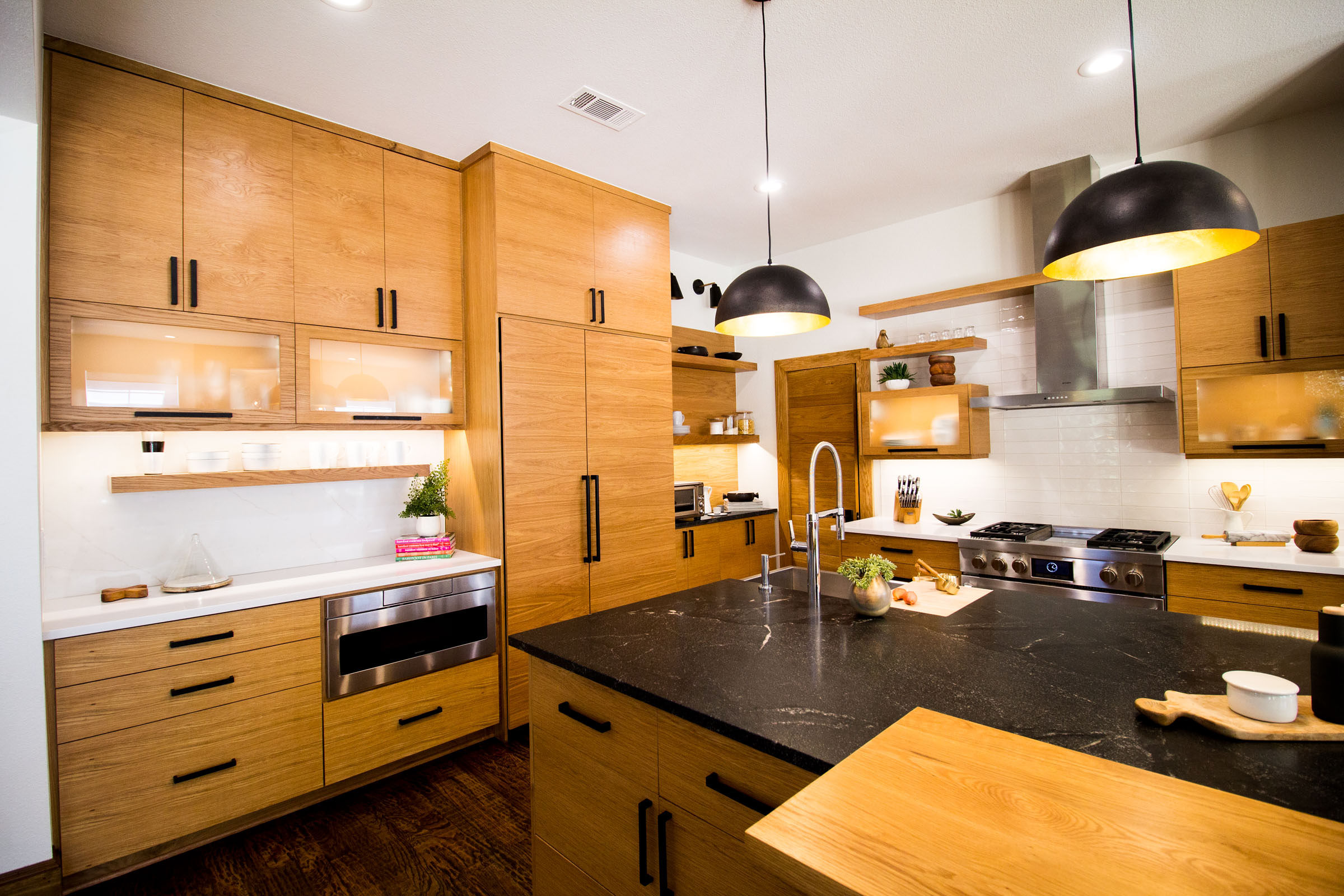 Scandinavian Kitchen Remodel with black counter slabs, blonde wood cabinets, black accents, minimalistic vibes