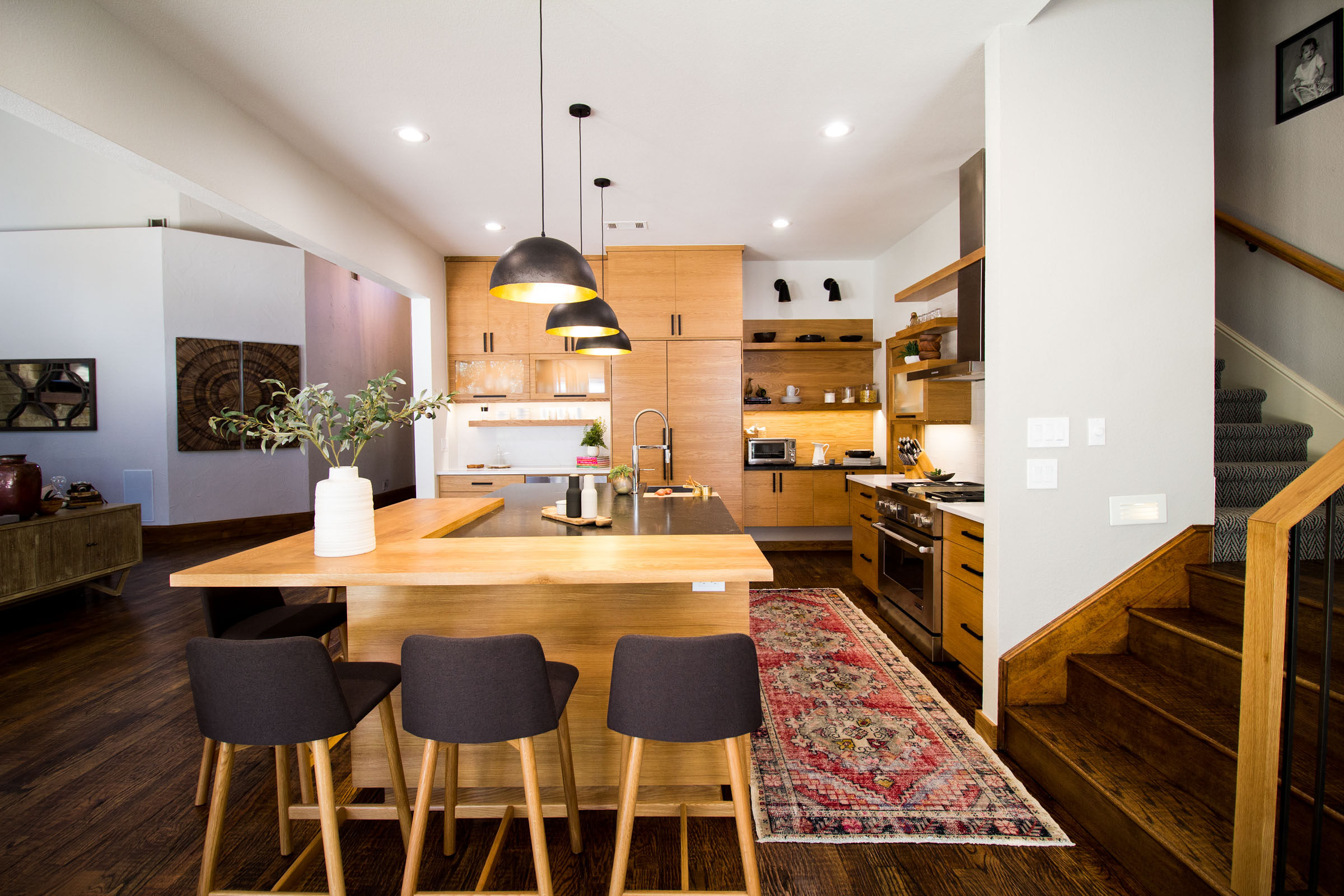 Kitchen island with a wood slab and black granite counters.