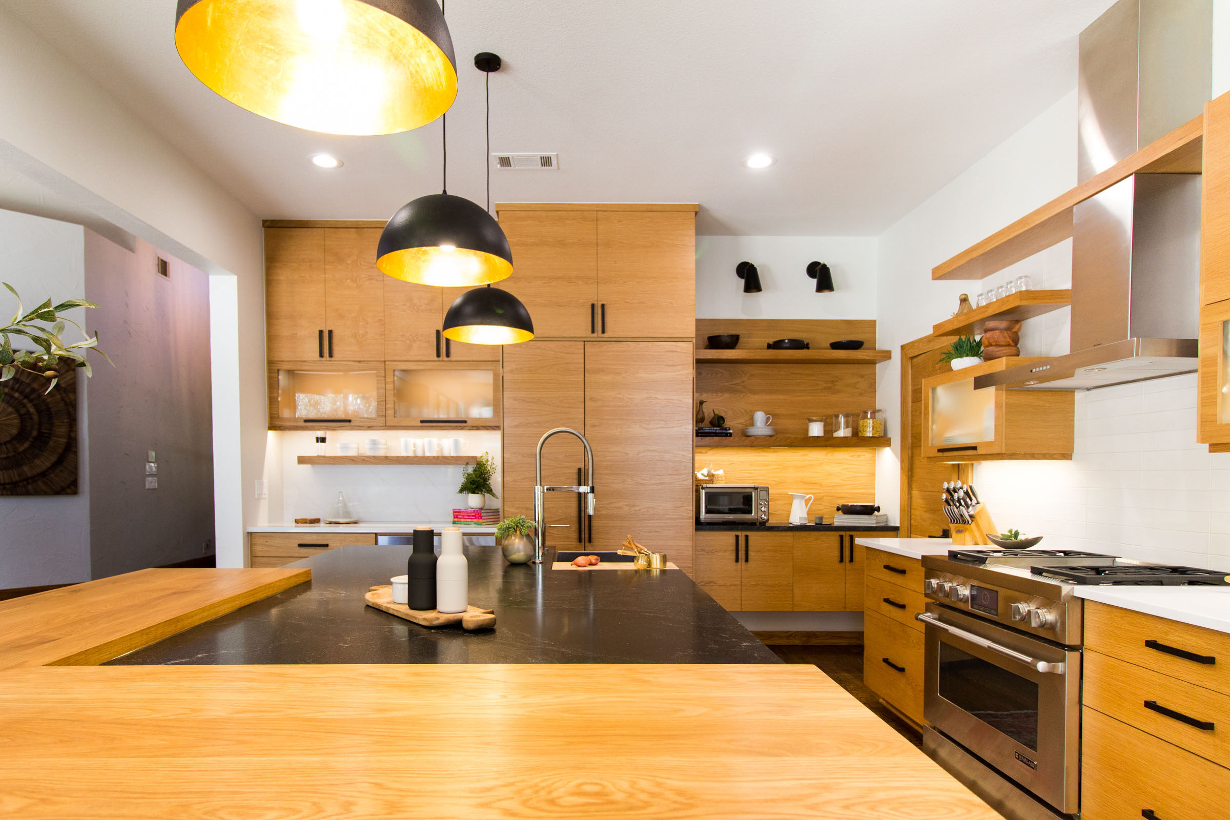 A picture capturing the beautiful blonde cabinets with a wood/granite island.