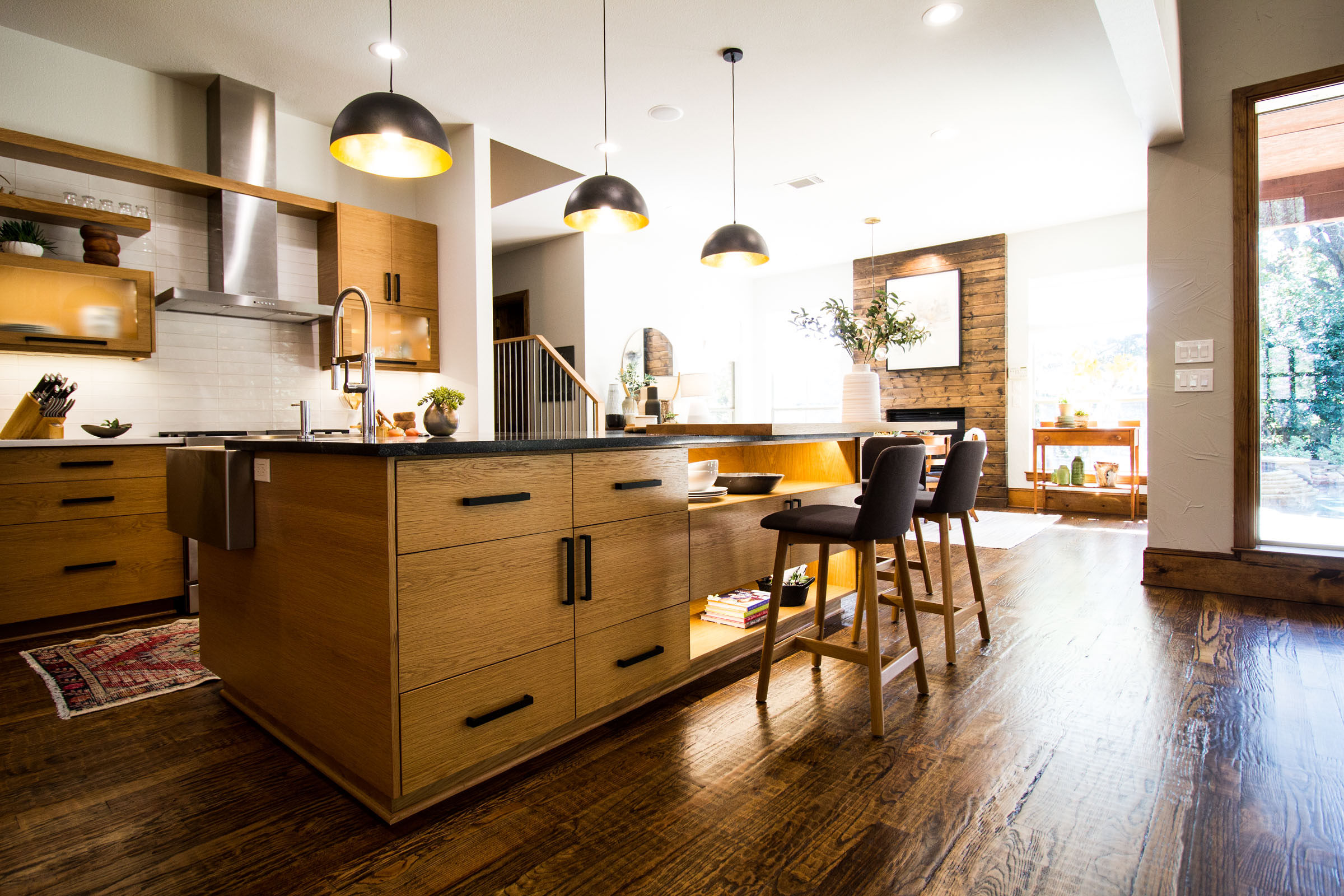 Full kitchen remodel with an open floor plan, hardwood floors, blonde wood cabinets, giant windows and fireplace.