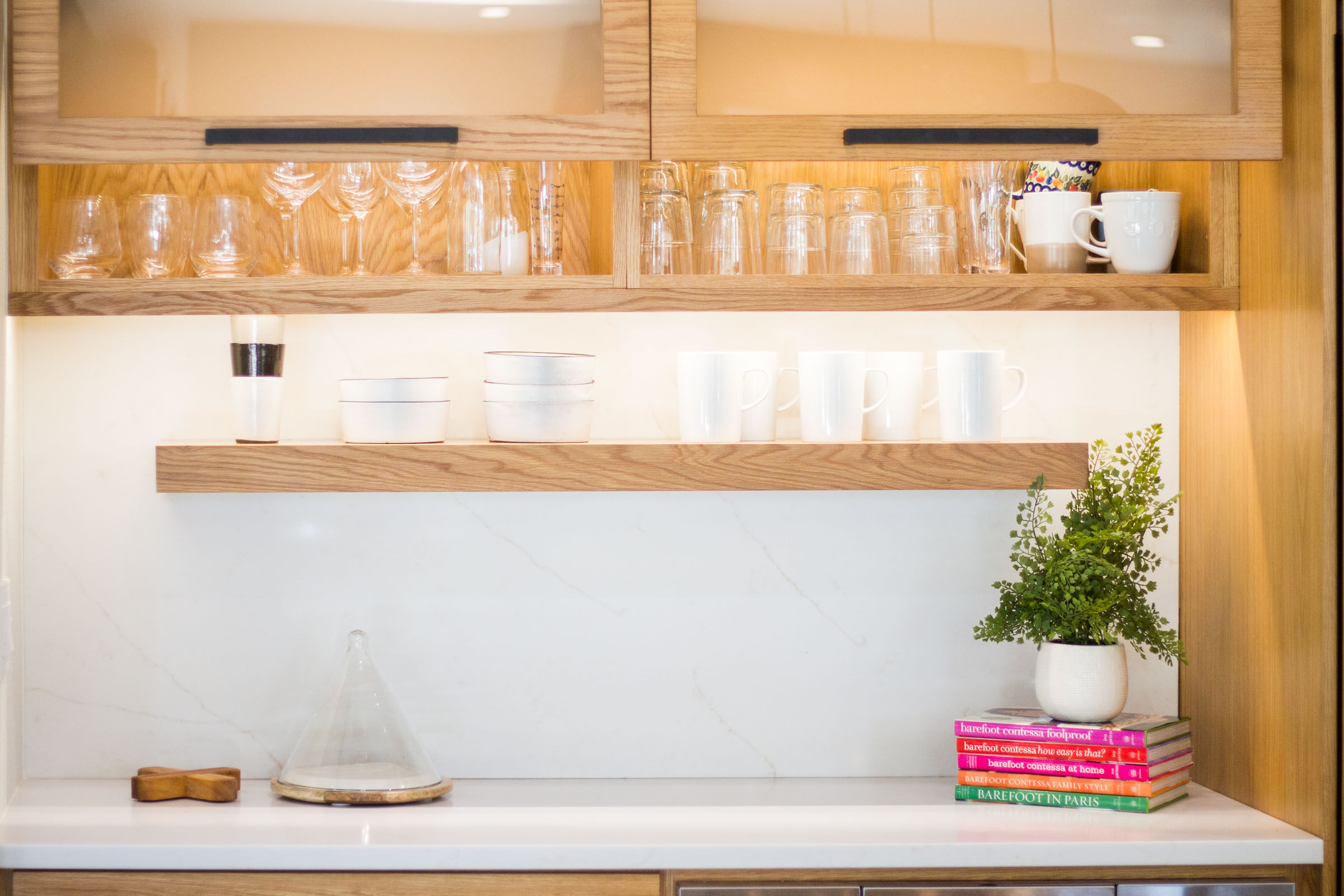 Exposed blonde wood shelving with glasses and mugs, books and minimalistic decor on white counters