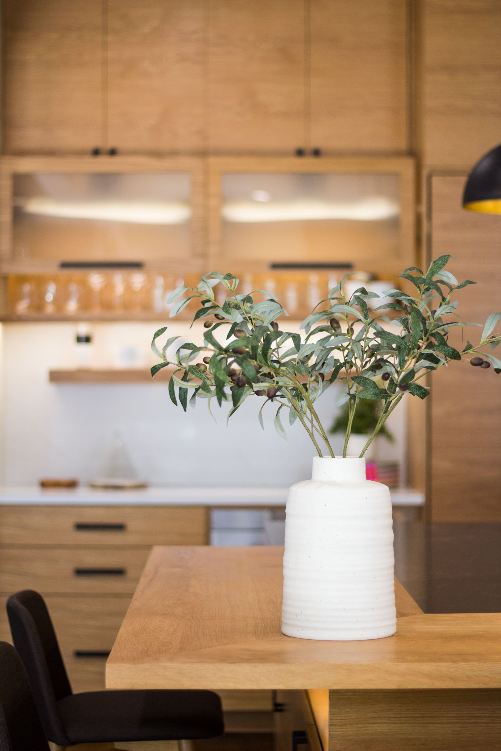 WHite ceramic vase with greenery on top of raw wood counter slab