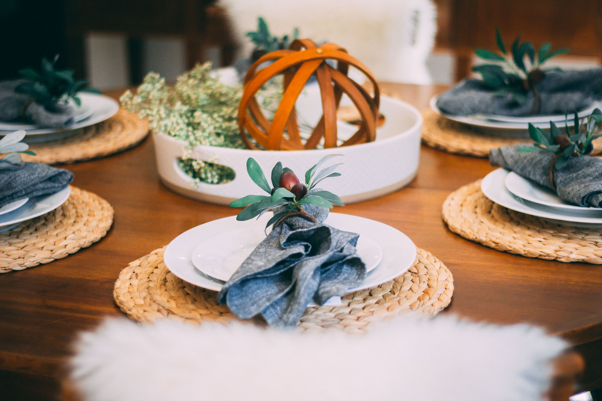 Table set up with center piece, braided basket chargers, grey napkins, dark wood table, white fur chair accent.