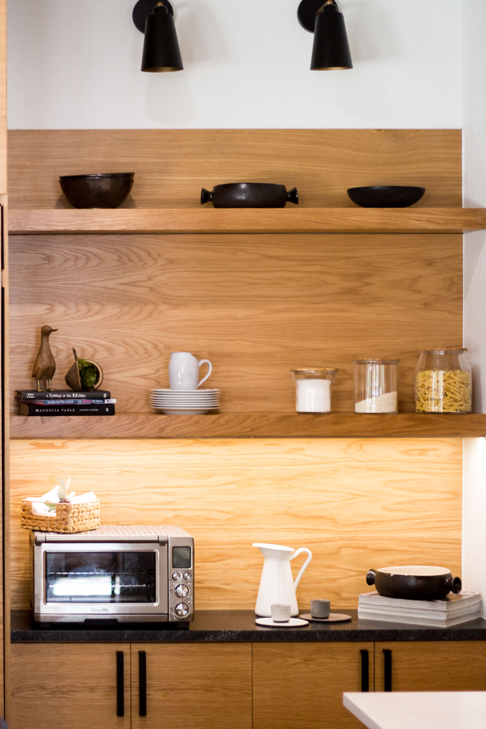 Exposed blonde wood shelves with decor and cookware, toaster oven, plates and under lighting.