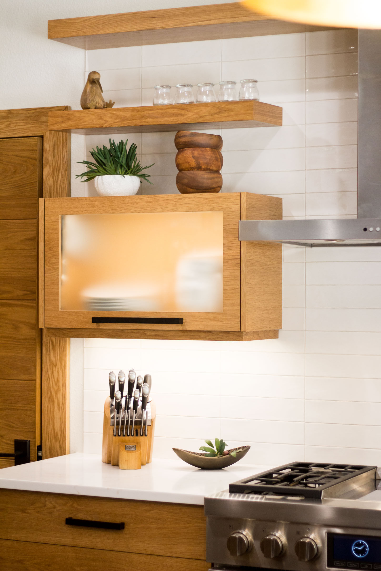 Stainless steel gas cooktop, exposed shelves, succulents, vertical lift cabinets made of blonde wood