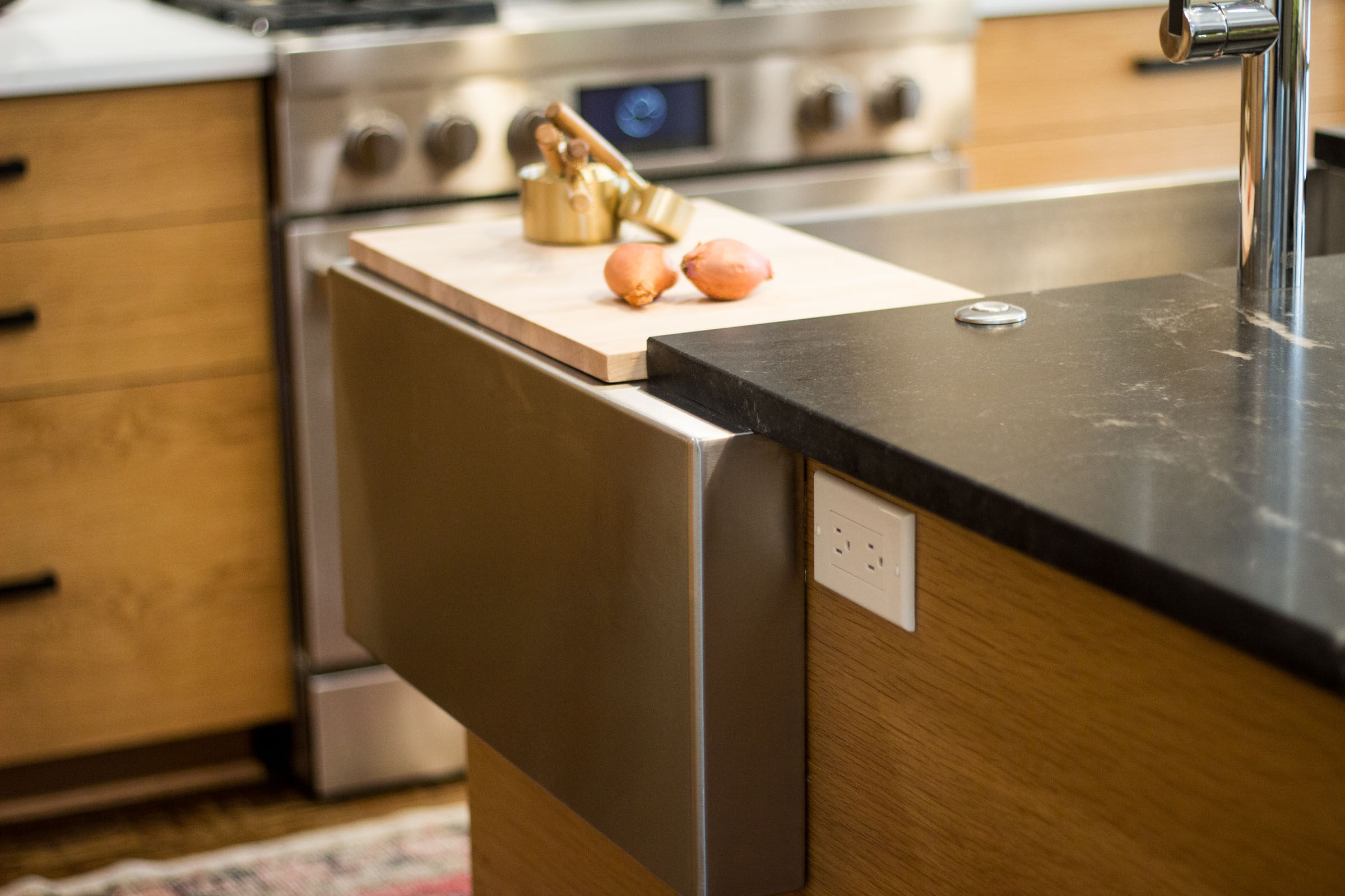Detail picture of a kitchen remodel with black granite, stainless steel appliances, and a raw wood cutting board.