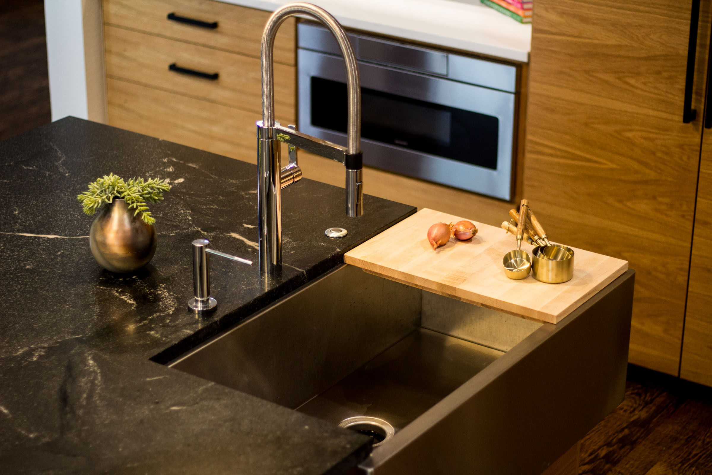 Black granite counter top, stainless steel swan kitchen faucet, cutting board onions and gold measuring cups with wooden handles.