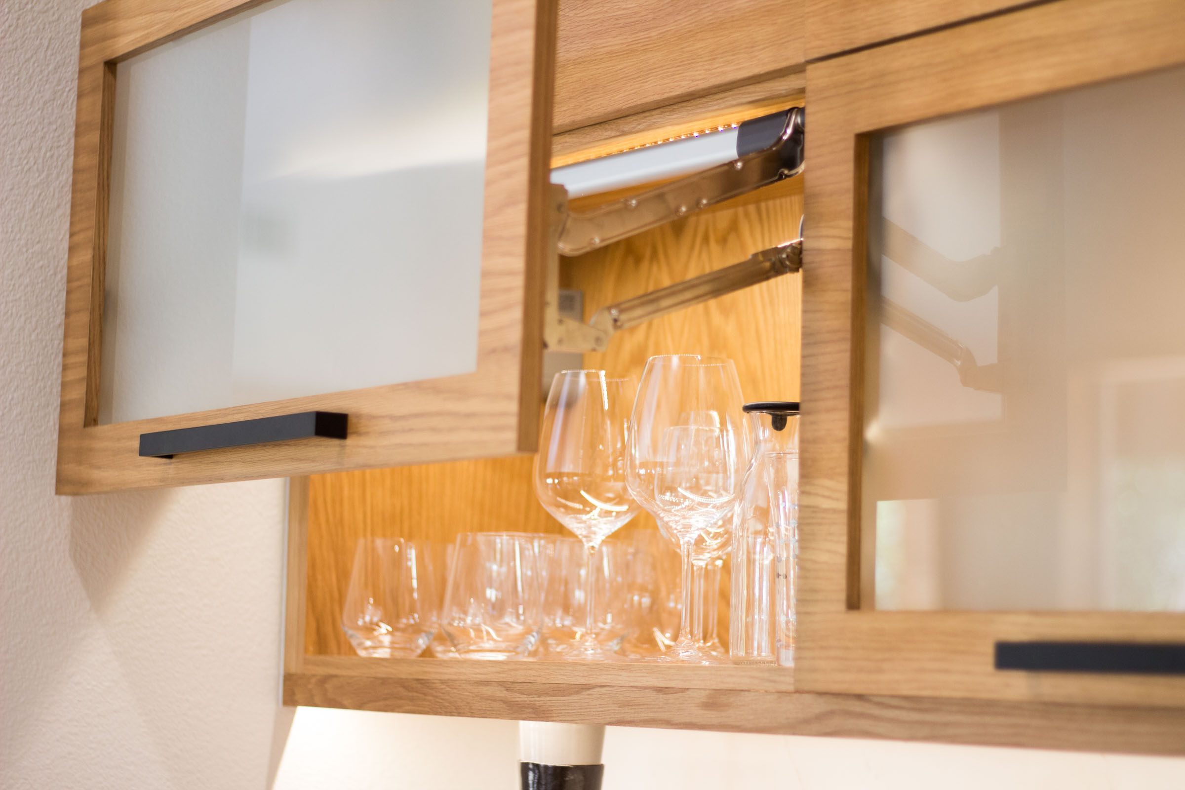 Wine glasses, frosted glass cabinet, vertical lift cabinet door, blonde wood