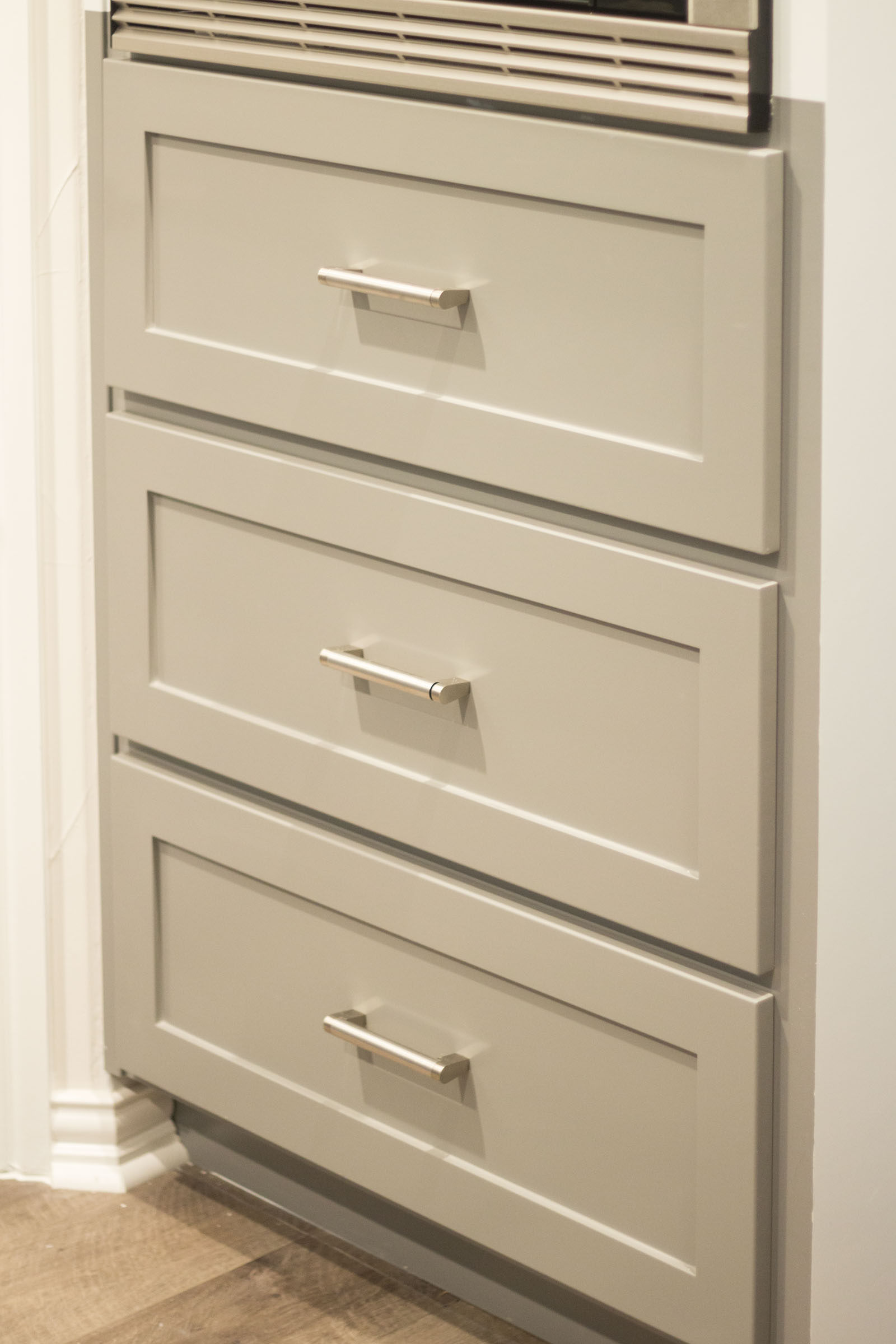 Close up photo of grey shaker style cabinet drawers and matte silver pulls