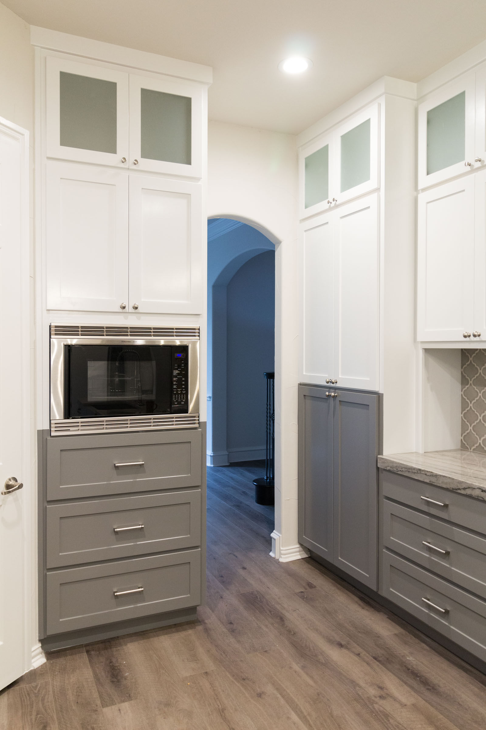 Contemporary kitchen remodel with grey and white cabinets, frosted glass, arabesque tile