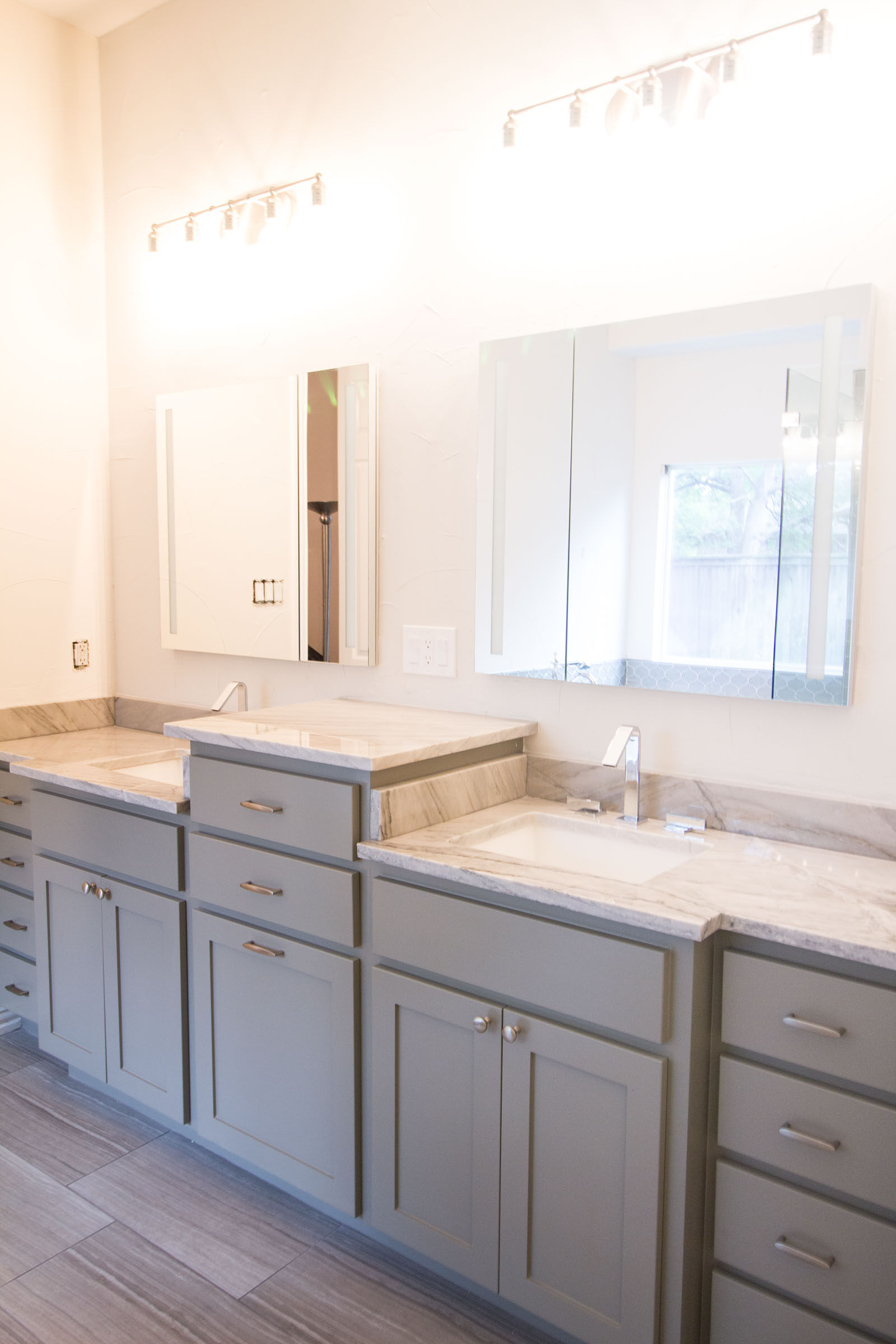 Contemporary bathroom remodel, grey cabinets, bright lighting, lots of counter space