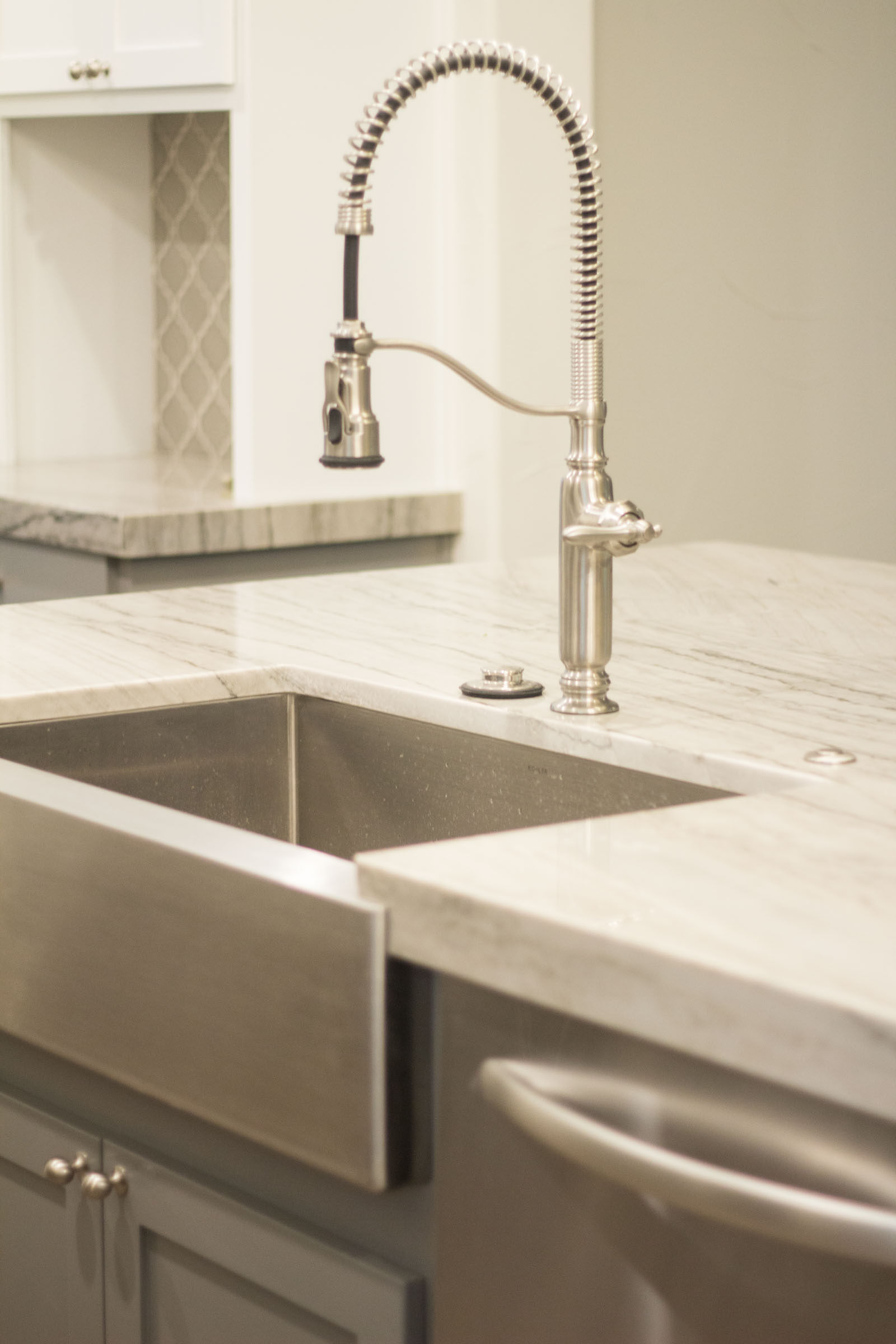 Farmhouse sink with high arch faucet, pull down sprayer, built in disposal button, stainless steel appliances