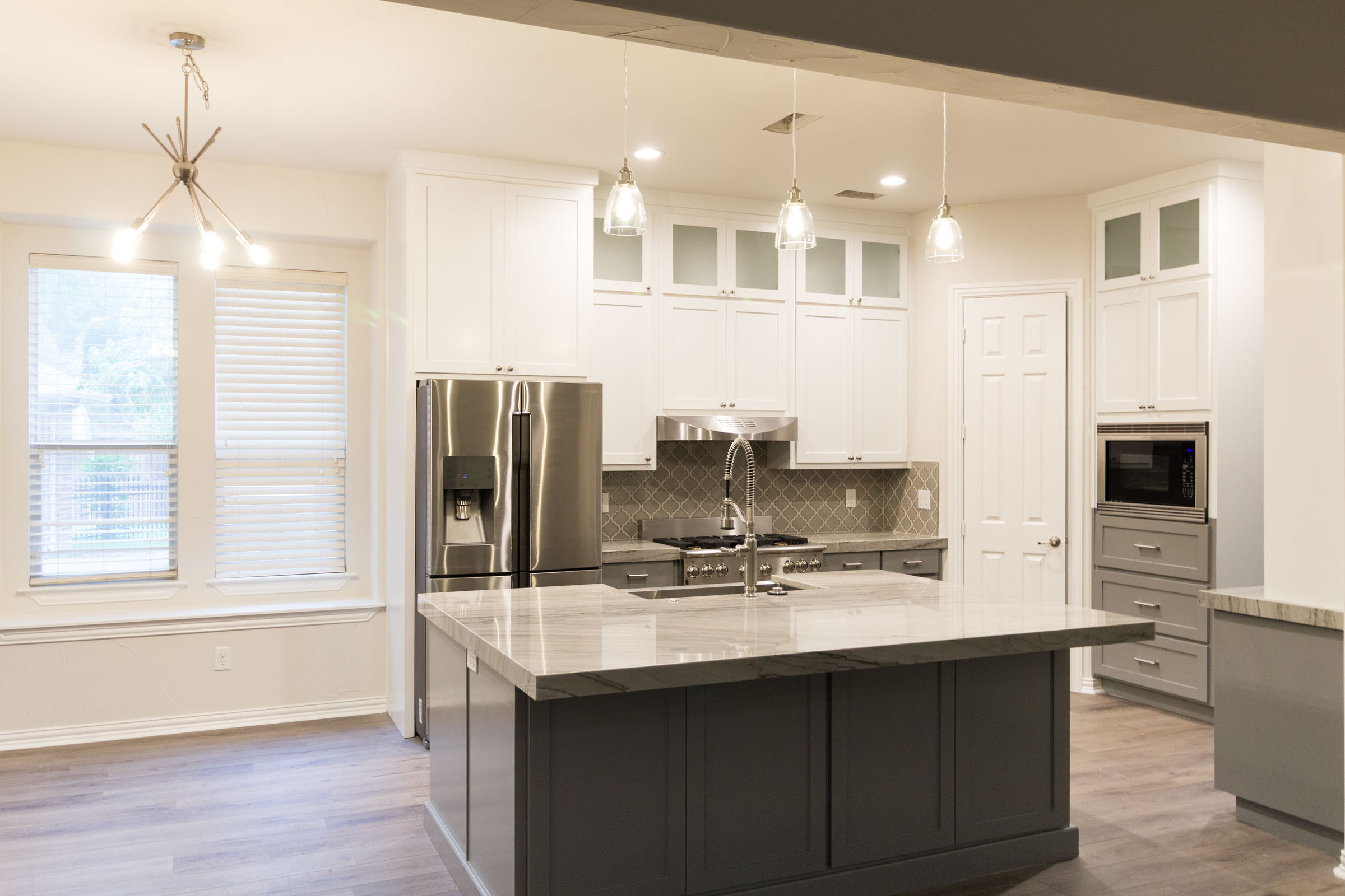 White angle picture of Contemporary kitchen remodel, grey and white, shaker cabinets, stainless steel, farmhouse sink, open floor plan