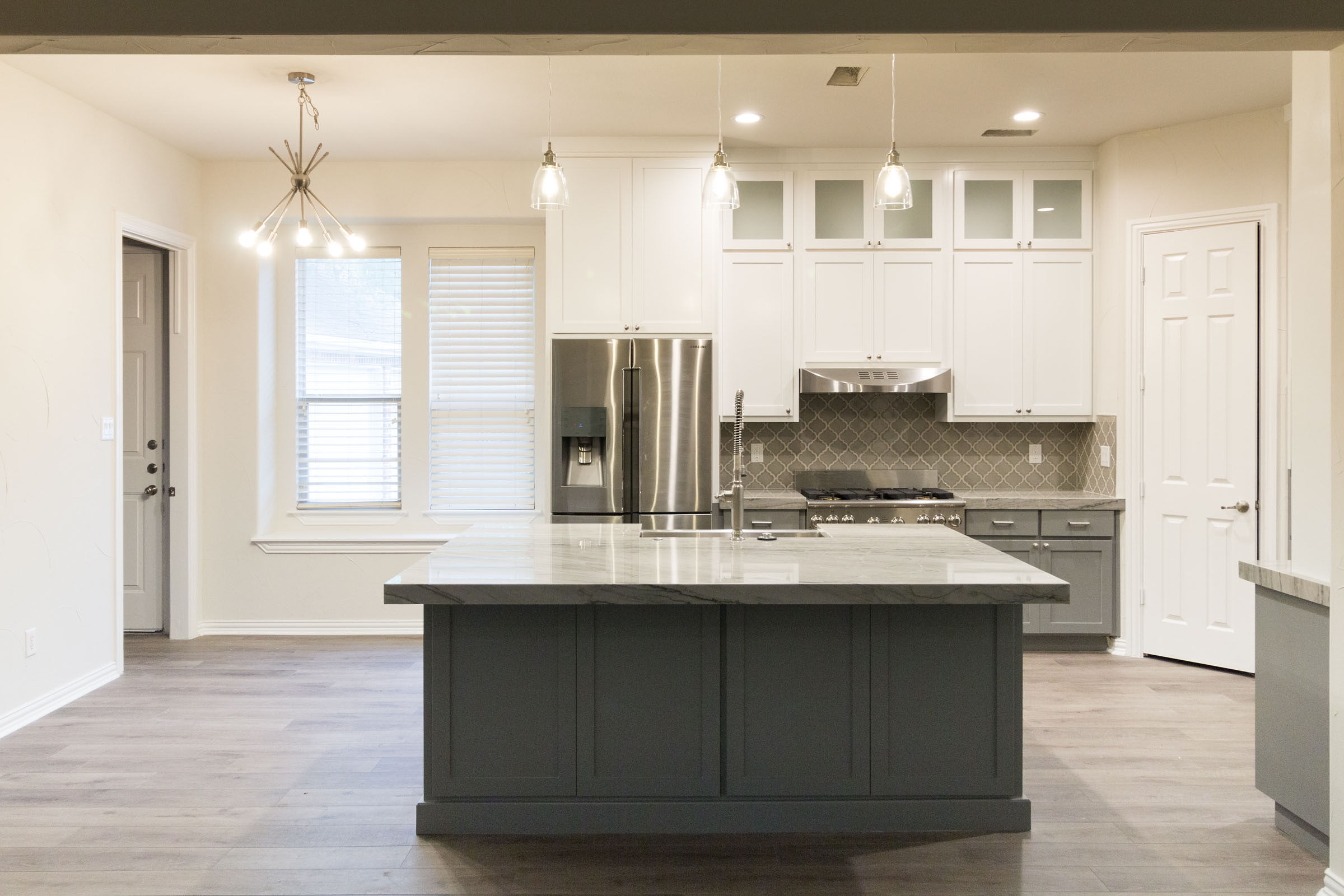 Wide angle shot of Contemporary kitchen remodel, grey and white, shaker cabinets, stainless steel, farmhouse sink, open floor plan