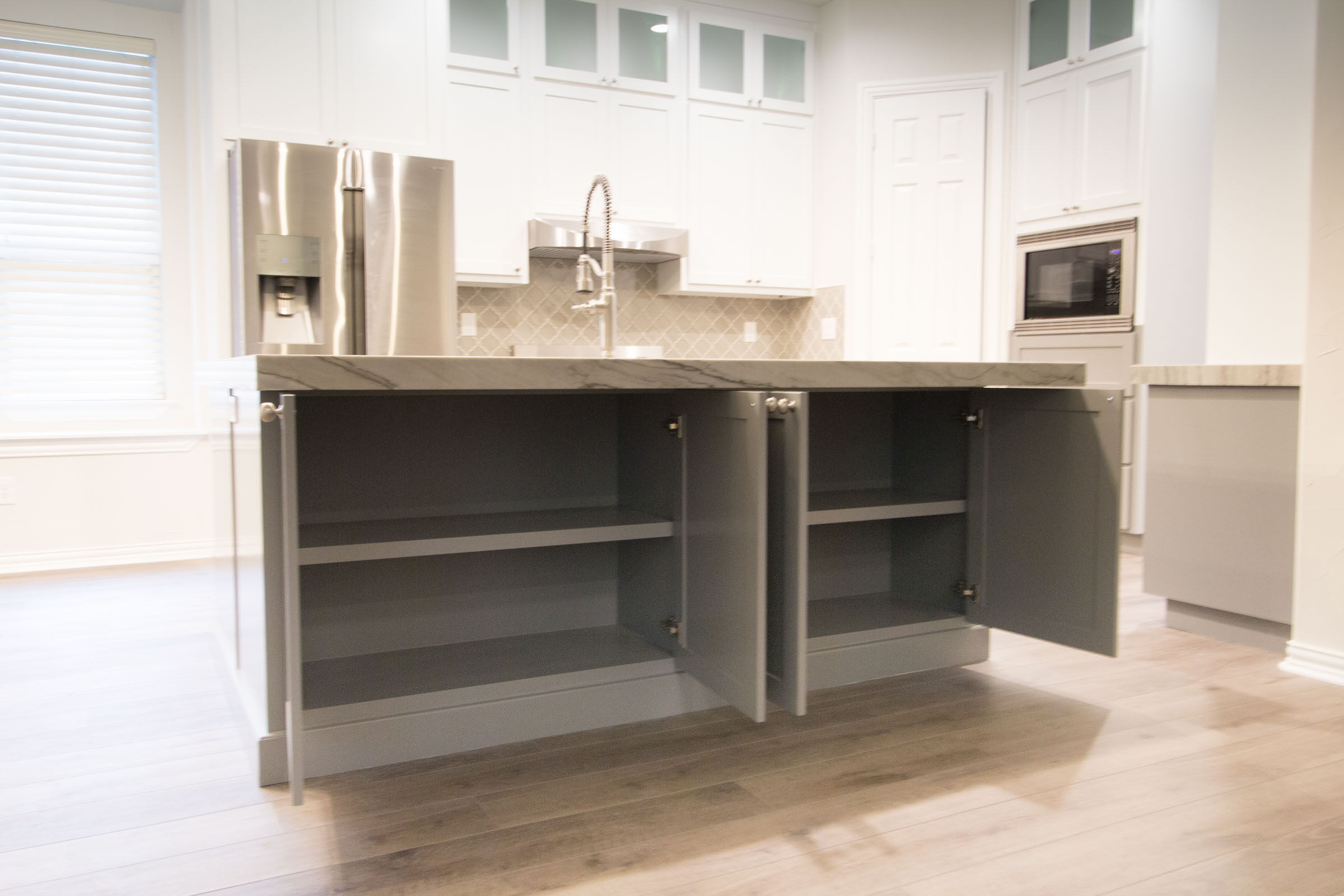 Contemporary kitchen remodel, showcasing under island storage space, open cabinet doors, bar island with sink