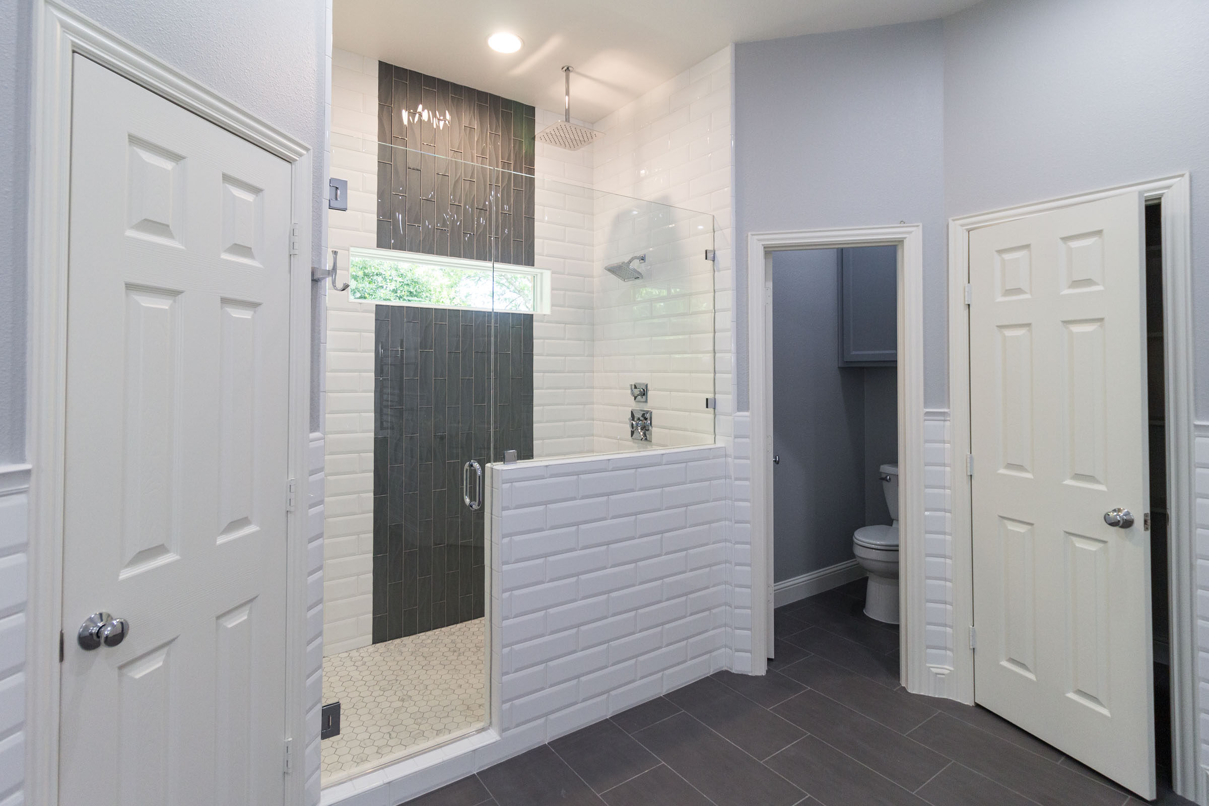 Contemporary bathroom remodel, grey and white, subway tile, grey flooring, toilet closet, walk in shower, chrome shower head