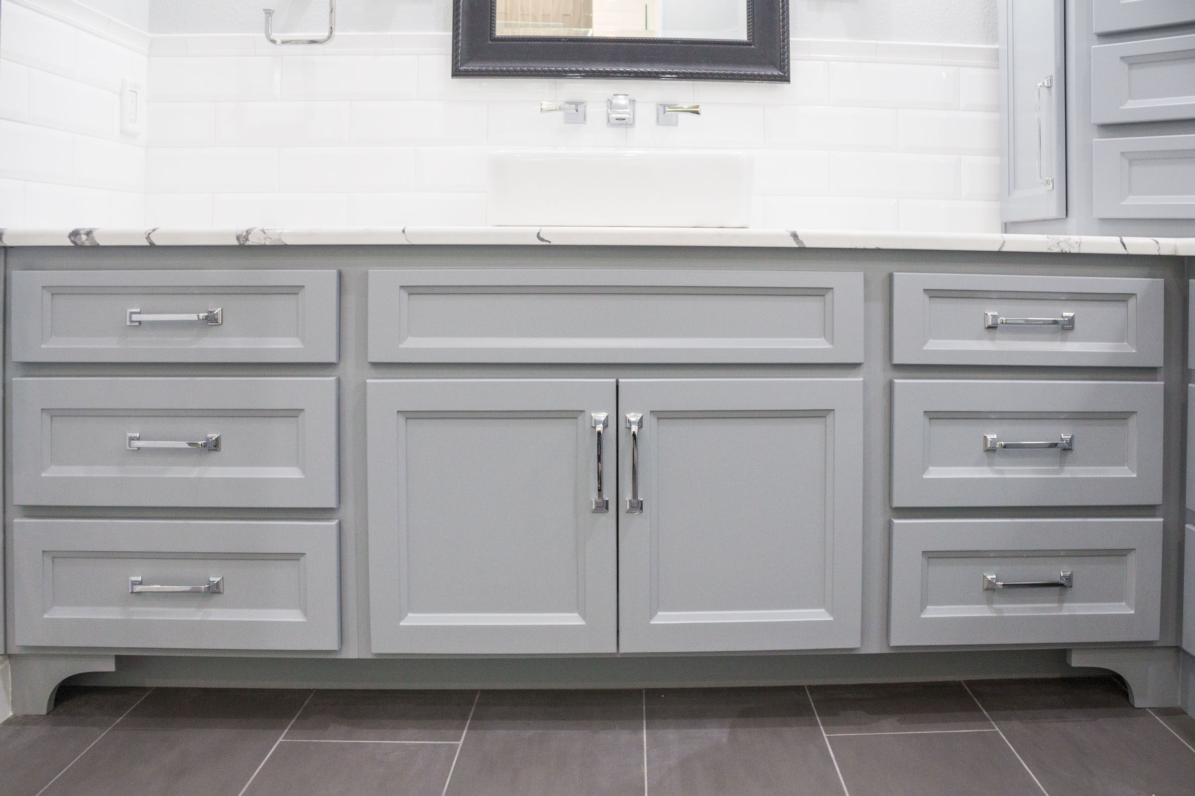 Contemporary bathroom remodel with grey cabinets, chrome hardware, white subway tile backsplash, and white/grey granite countertops