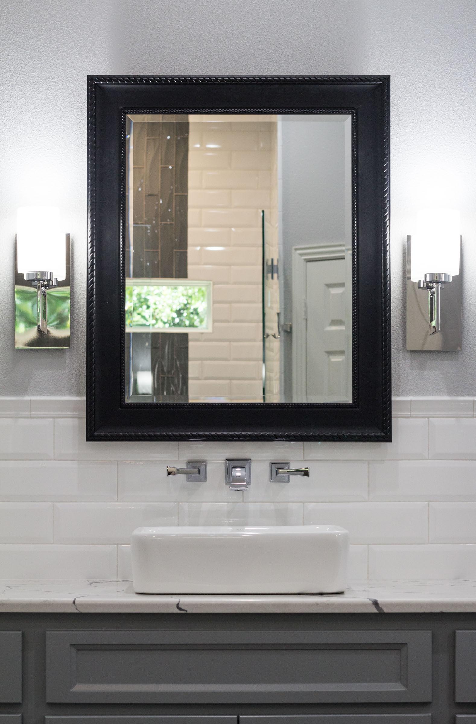 White subway tile backsplash, pedestal sink, chrome hardware, black trimmed mirror, grey shaker cabinets