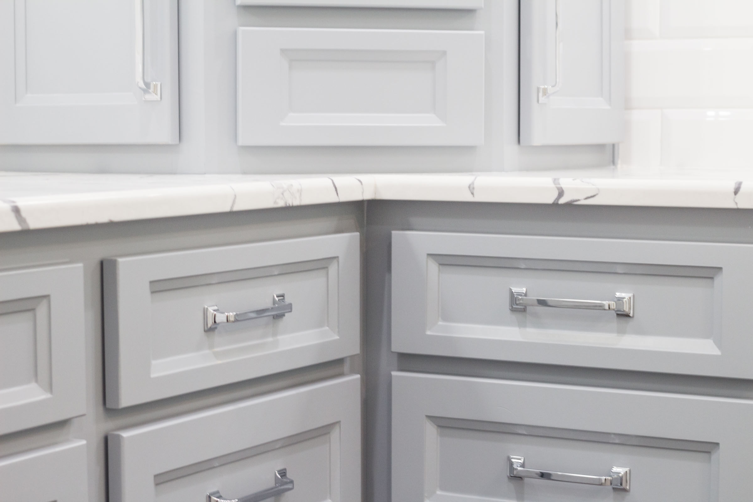Close up of contemporary bathroom cabinets, shaker style, chrome drawer hardware, white and grey mixed granite