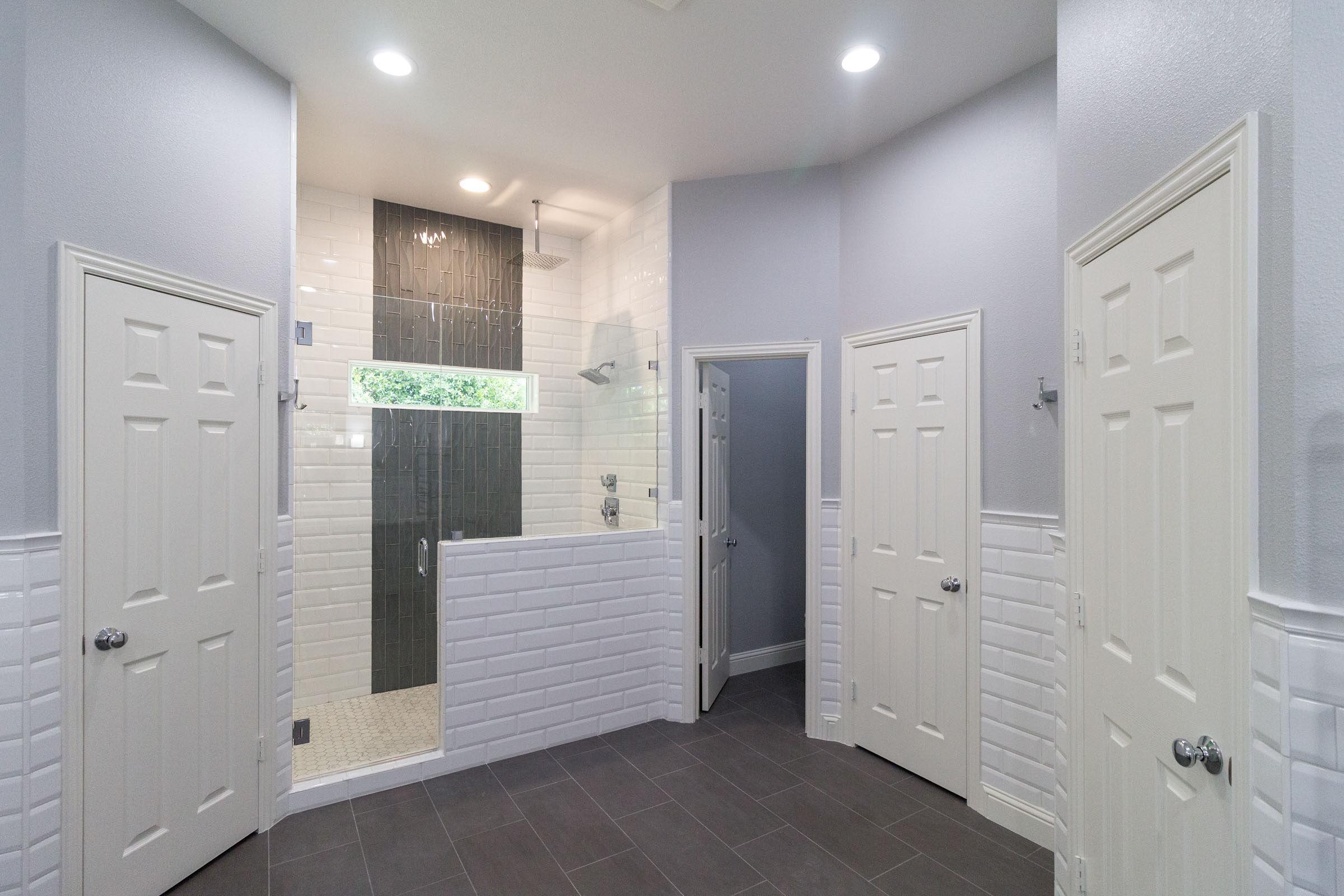 Bathroom remodel with white subway tile, dark grey flooring, walk in shower, open concept
