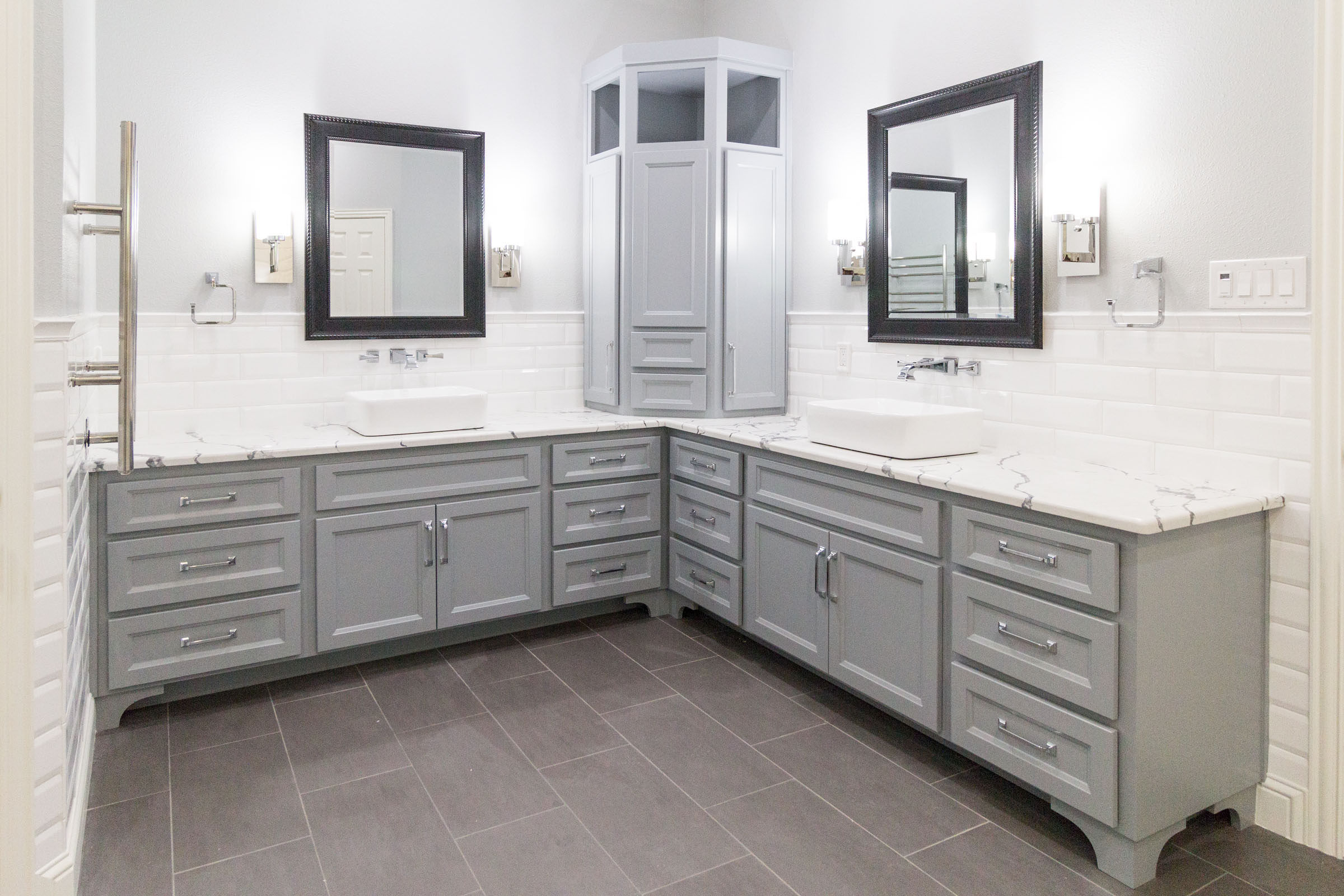 Contemporary styled bathroom remodel, grey shaker cabinets, white marble counters, dark grey trimmed vanity mirrors, jack and jill, white backsplash, grey paint