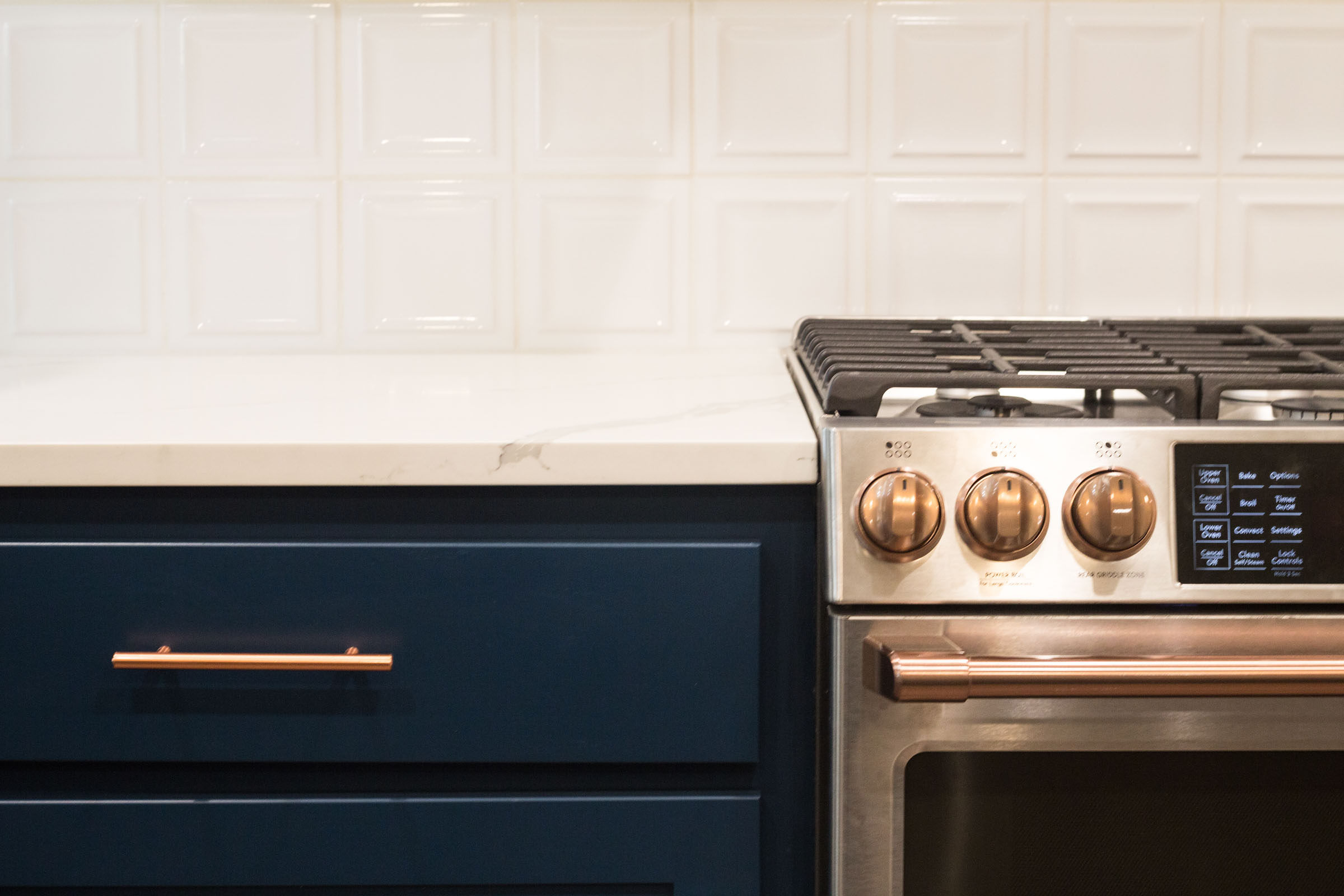 Navy drawers, stainless steel gas range, copper accents, kitchen remodel