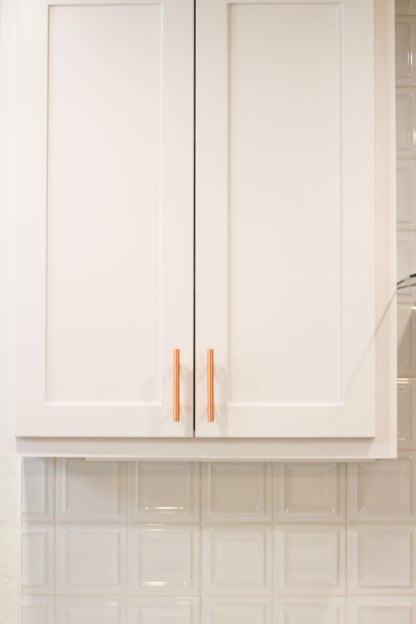 White shaker cabinets and backsplash with copper hardware