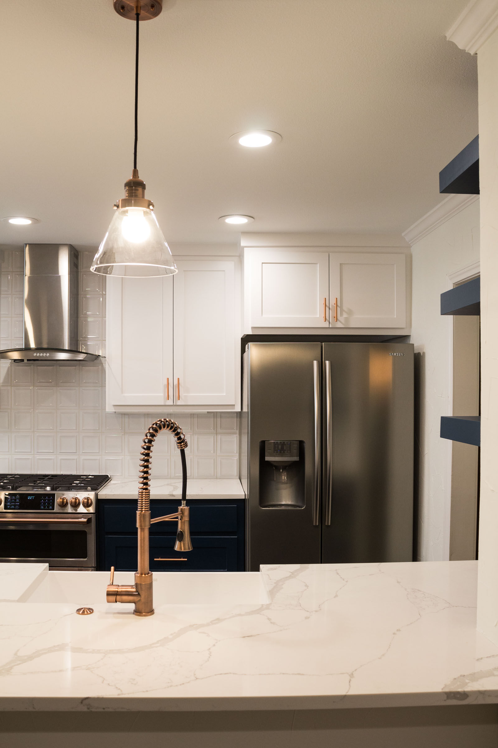 Kitchen remodel with white counters, navy cabinets, and copper hardware