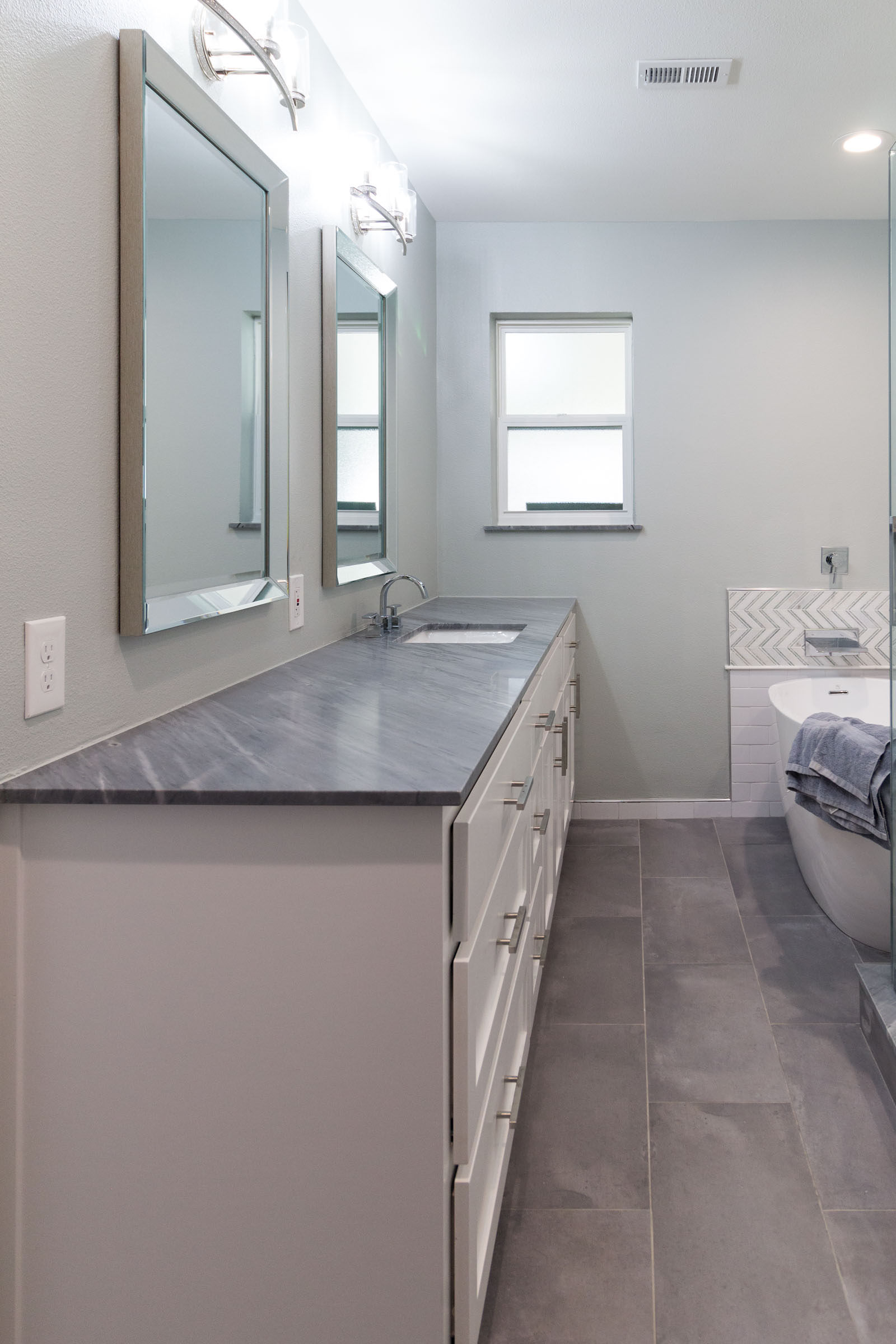 Grey counter tops and flooring, white cabinets, bathtub, small window, remodel project