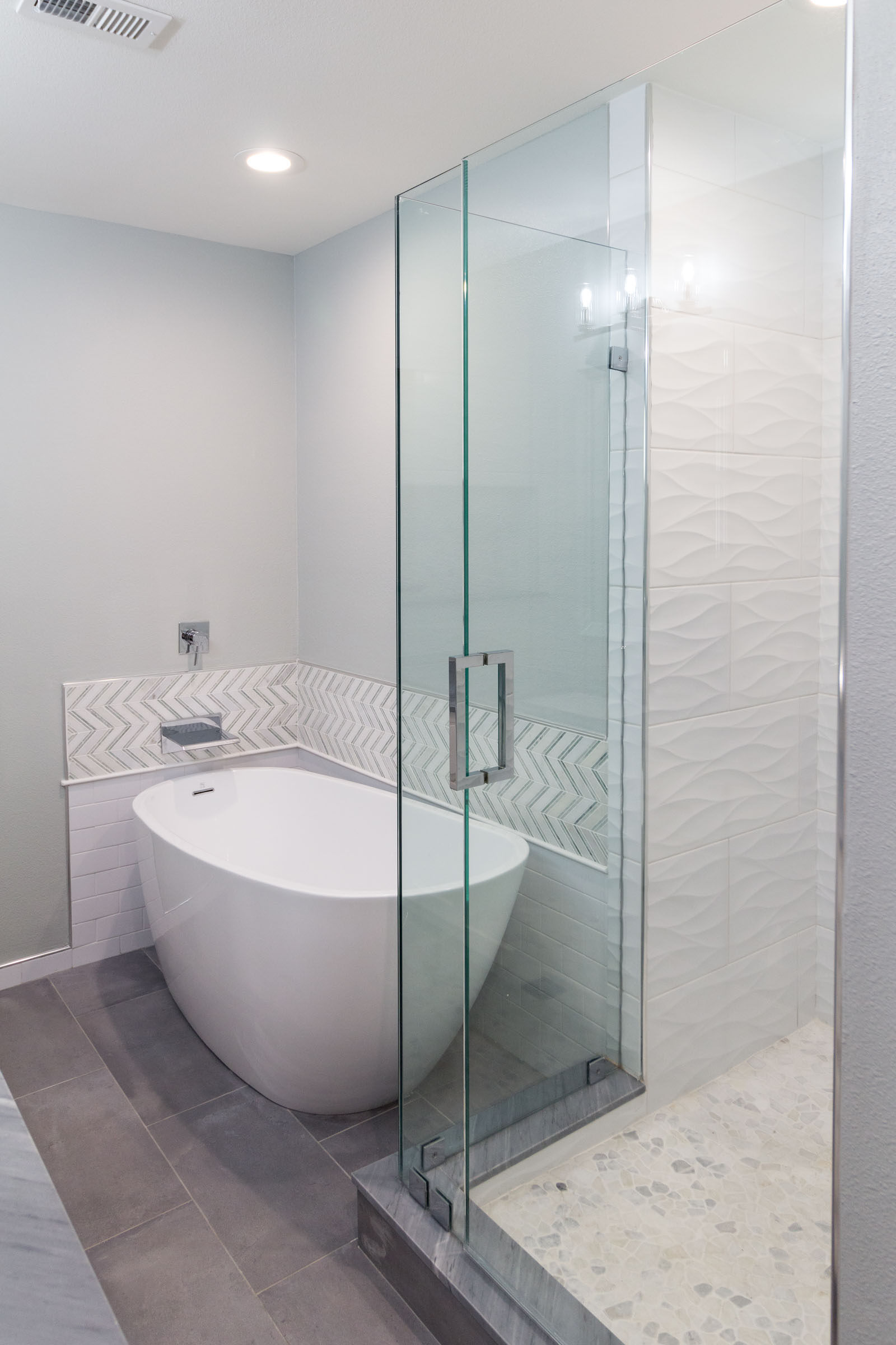 Grey and white bathroom remodel, pedestal tub, waterfall faucet, chrome accents, walkin shower