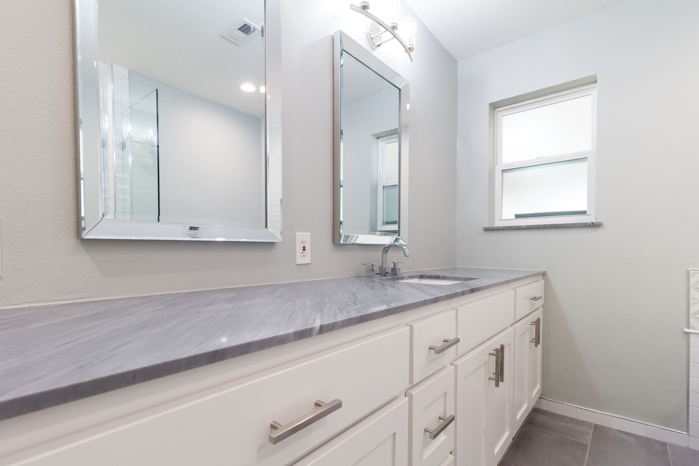Bathroom remodel, twin mirrors, white shaker cabinets, grey granite, window, dark grey tile