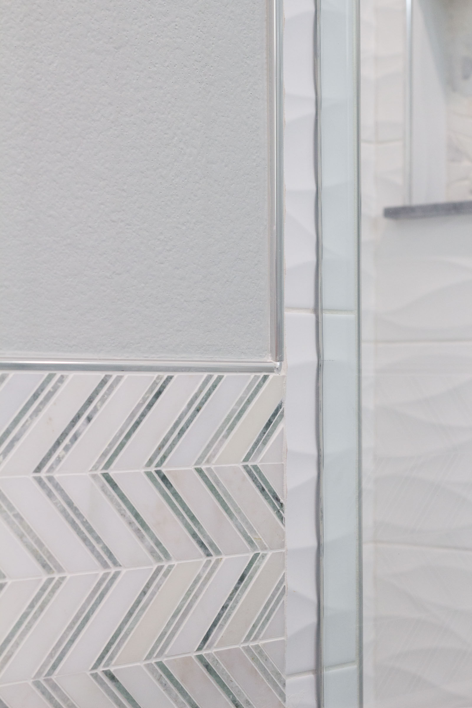 Bathroom remodel with chevron white and grey tile, soft grey paint, and stainless steel bullnose